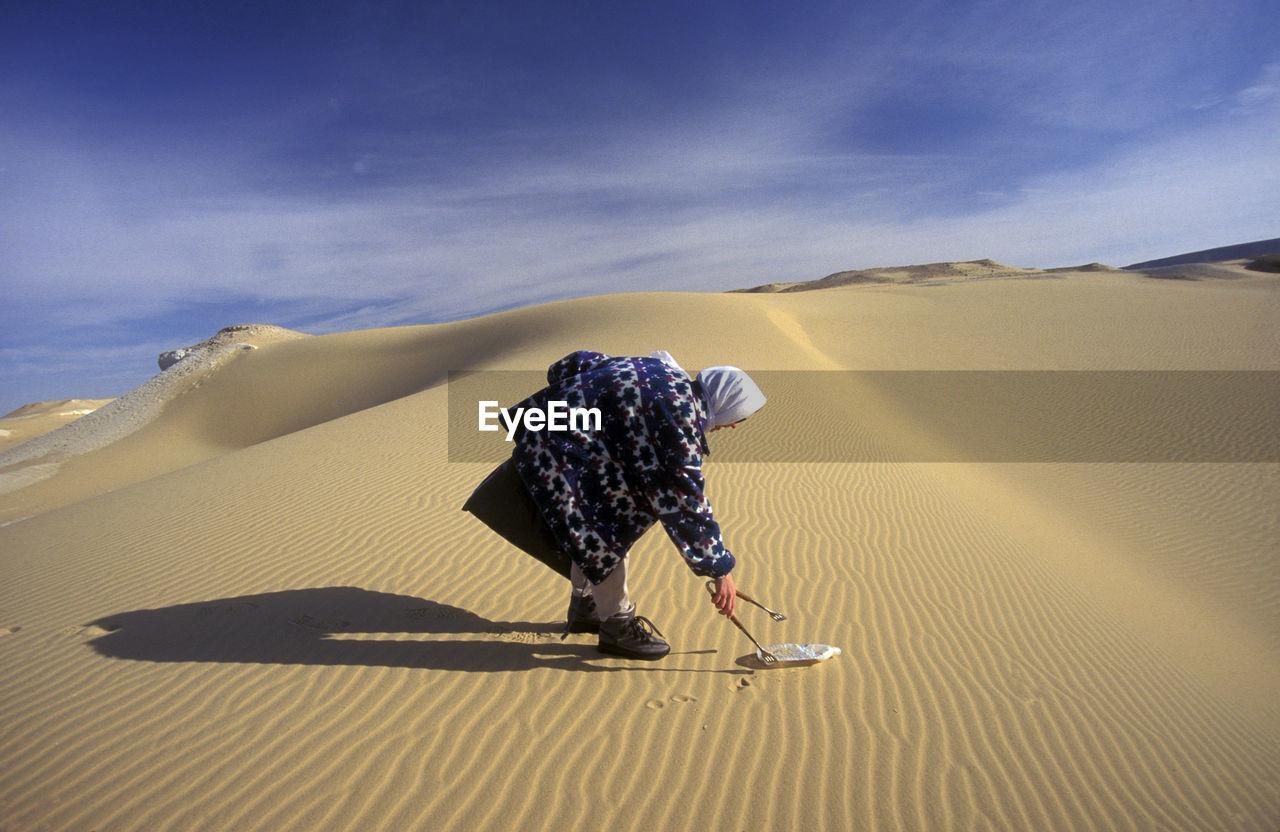 Side View Of Man Picking Up Plastic Bottle On Desert