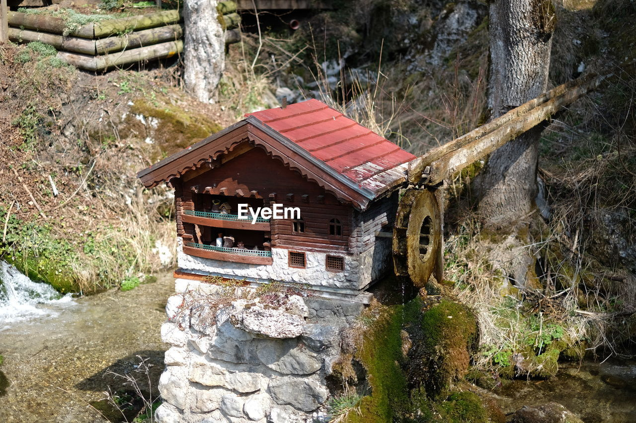 architecture, built structure, tree, day, nature, no people, wood - material, plant, forest, water, solid, rock, building exterior, rock - object, outdoors, land, tranquility, abandoned, water wheel, flowing water, stream - flowing water, stone wall