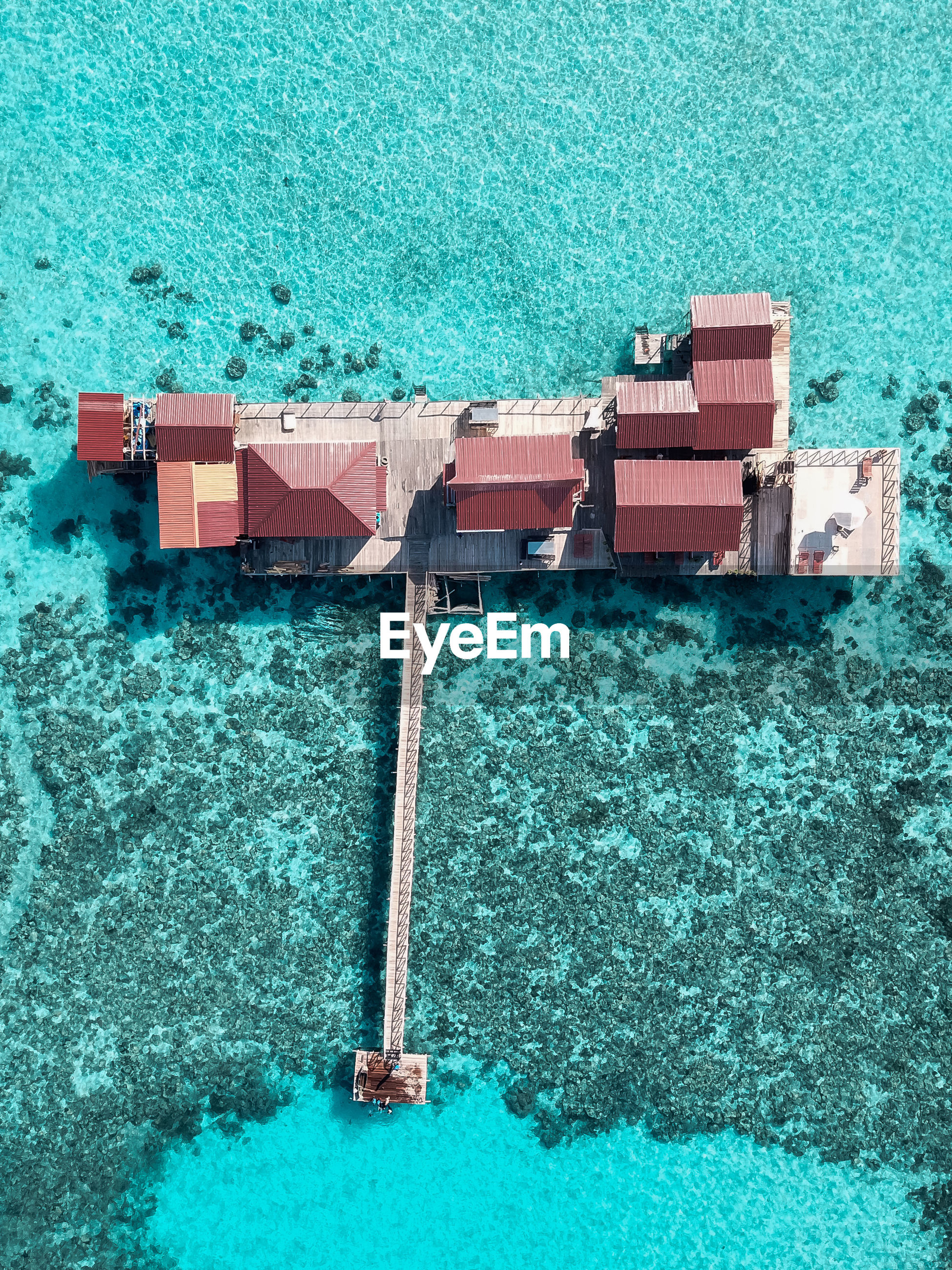 Aerial view of a tropical island in turquoise water. water villas on tropical island resort.