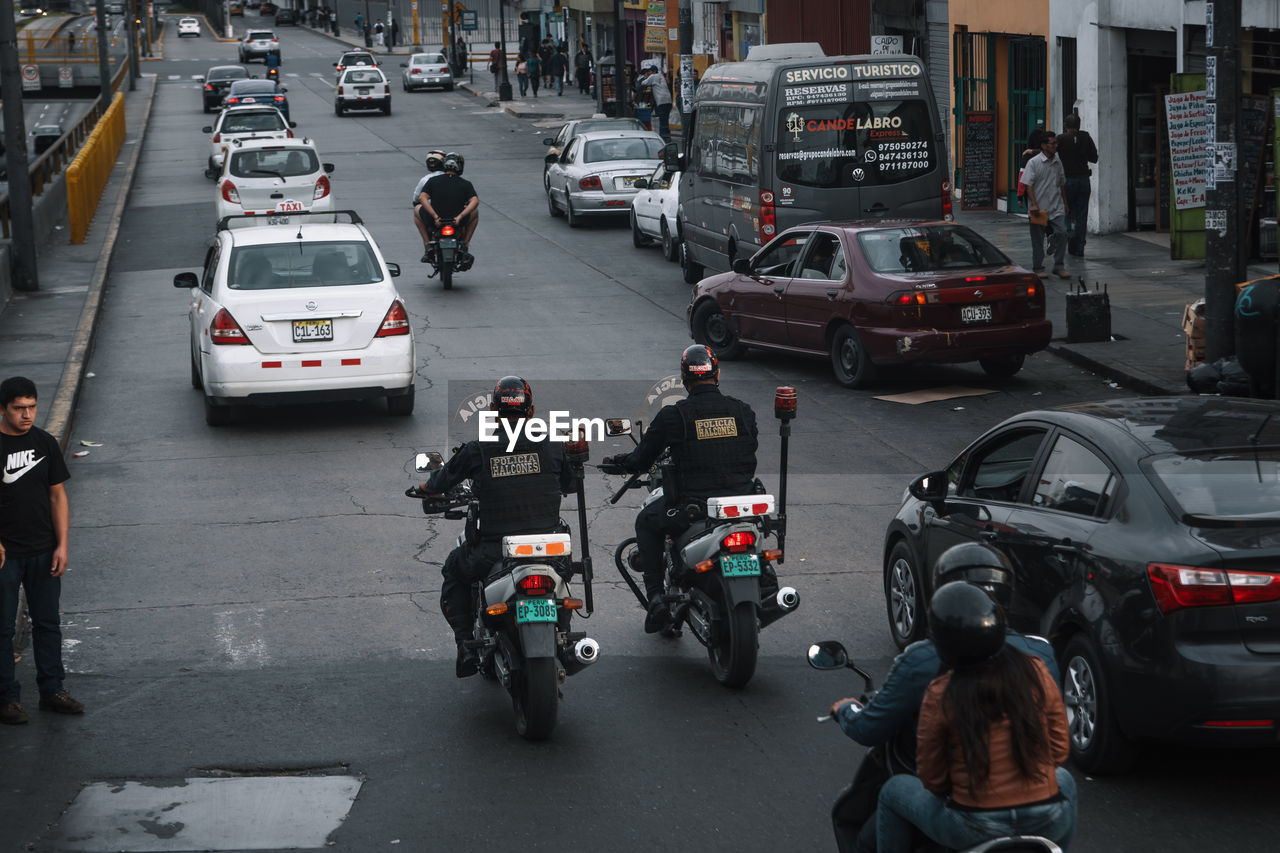 mode of transportation, transportation, motor vehicle, car, land vehicle, city, street, road, traffic, real people, architecture, group of people, motorcycle, city life, people, men, built structure, city street, incidental people, lifestyles, riding