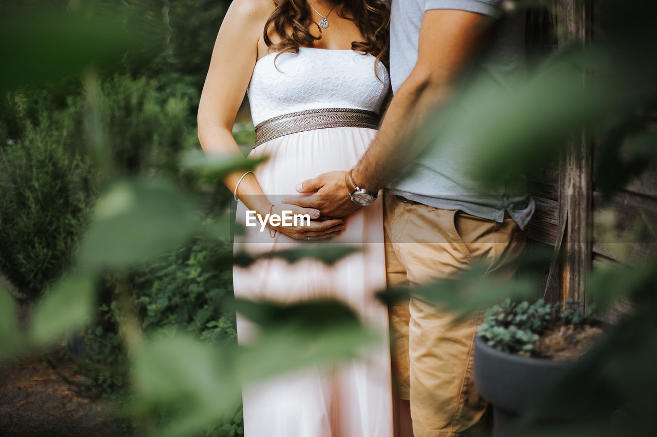 Midsection of man holding pregnant wife while standing by plants