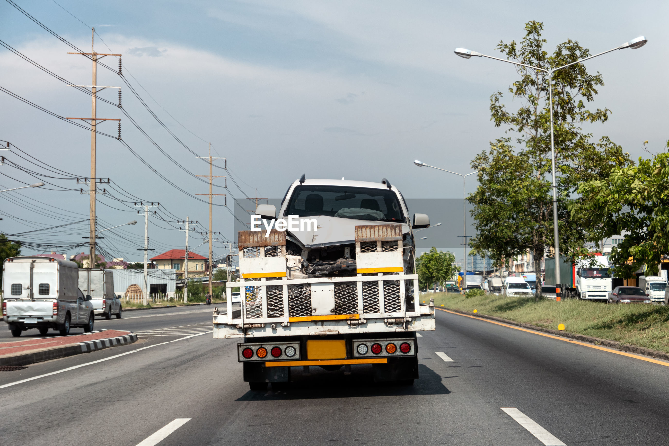 VEHICLES ON ROAD AGAINST SKY