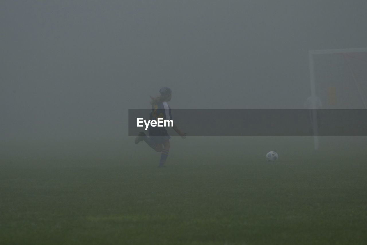 soccer, grass, sport, one person, playing, fog, ball, full length, soccer ball, real people, outdoors, soccer player, night, soccer uniform, soccer field, golf, golf course, golfer, sportsman, sky, young adult, people