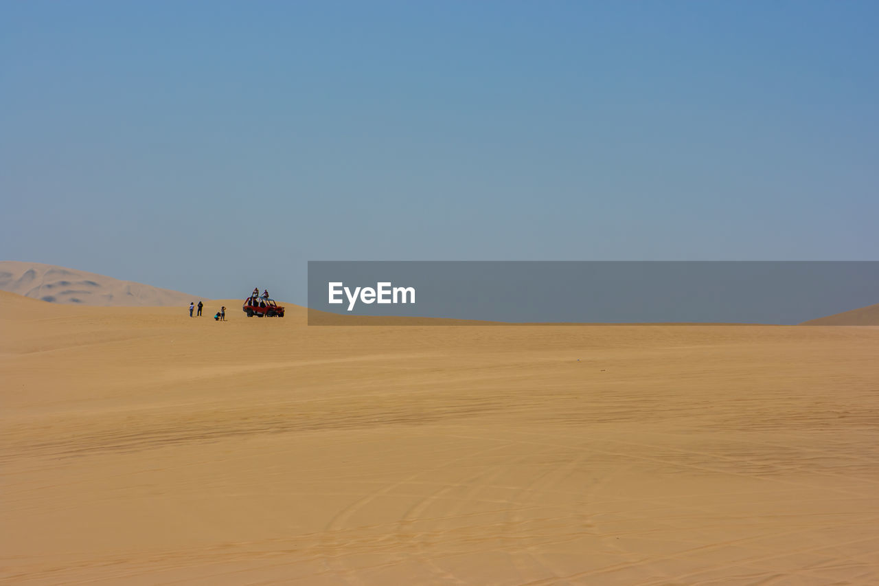 Distant View Of People On Desert Against Clear Sky