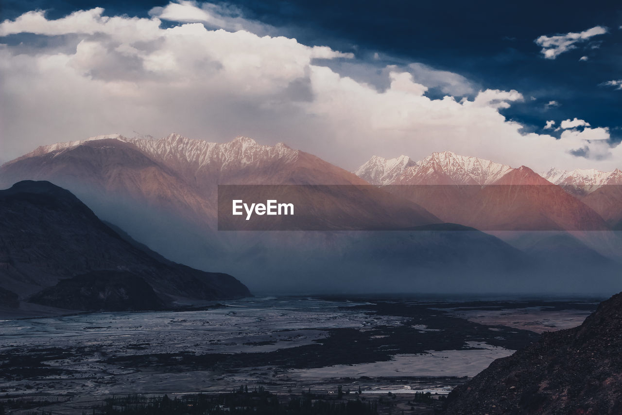 PANORAMIC VIEW OF SEA BY MOUNTAINS AGAINST SKY