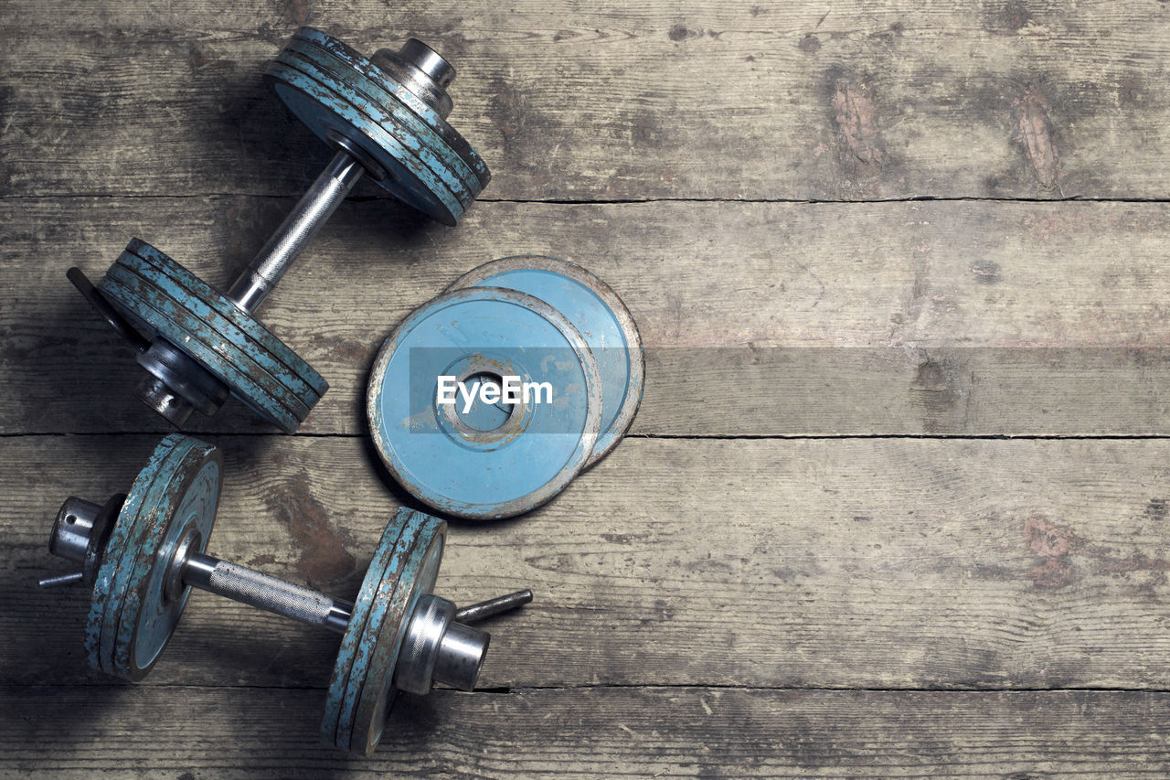 High Angle View Of Weights On Wooden Floor