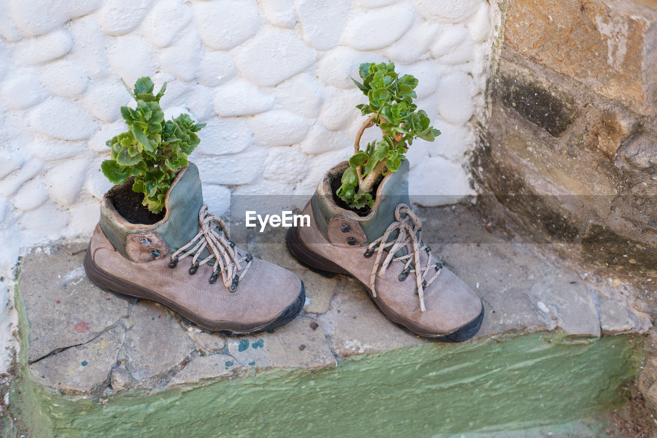 HIGH ANGLE VIEW OF SHOES BY WATER