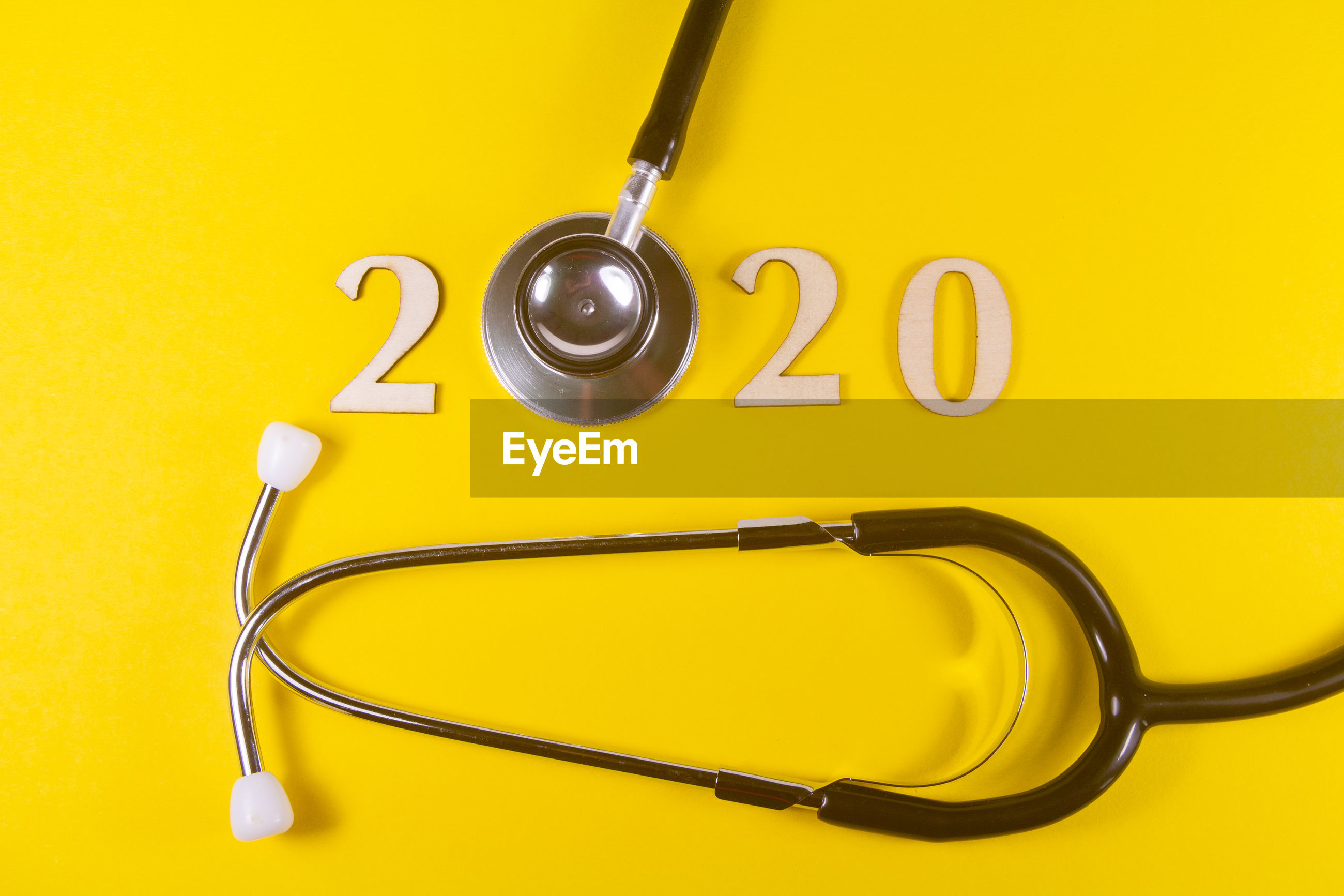 Directly above shot of stethoscope with number over yellow background