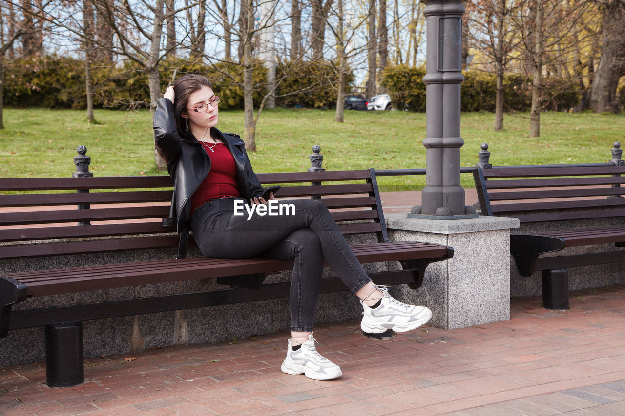 WOMAN SITTING ON BENCH AT PARK