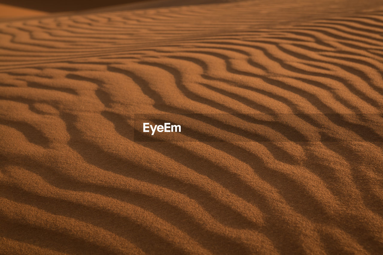 sand, land, pattern, landscape, desert, climate, sand dune, scenics - nature, arid climate, no people, wave pattern, natural pattern, full frame, backgrounds, environment, tranquility, nature, high angle view, brown, beauty in nature, atmospheric