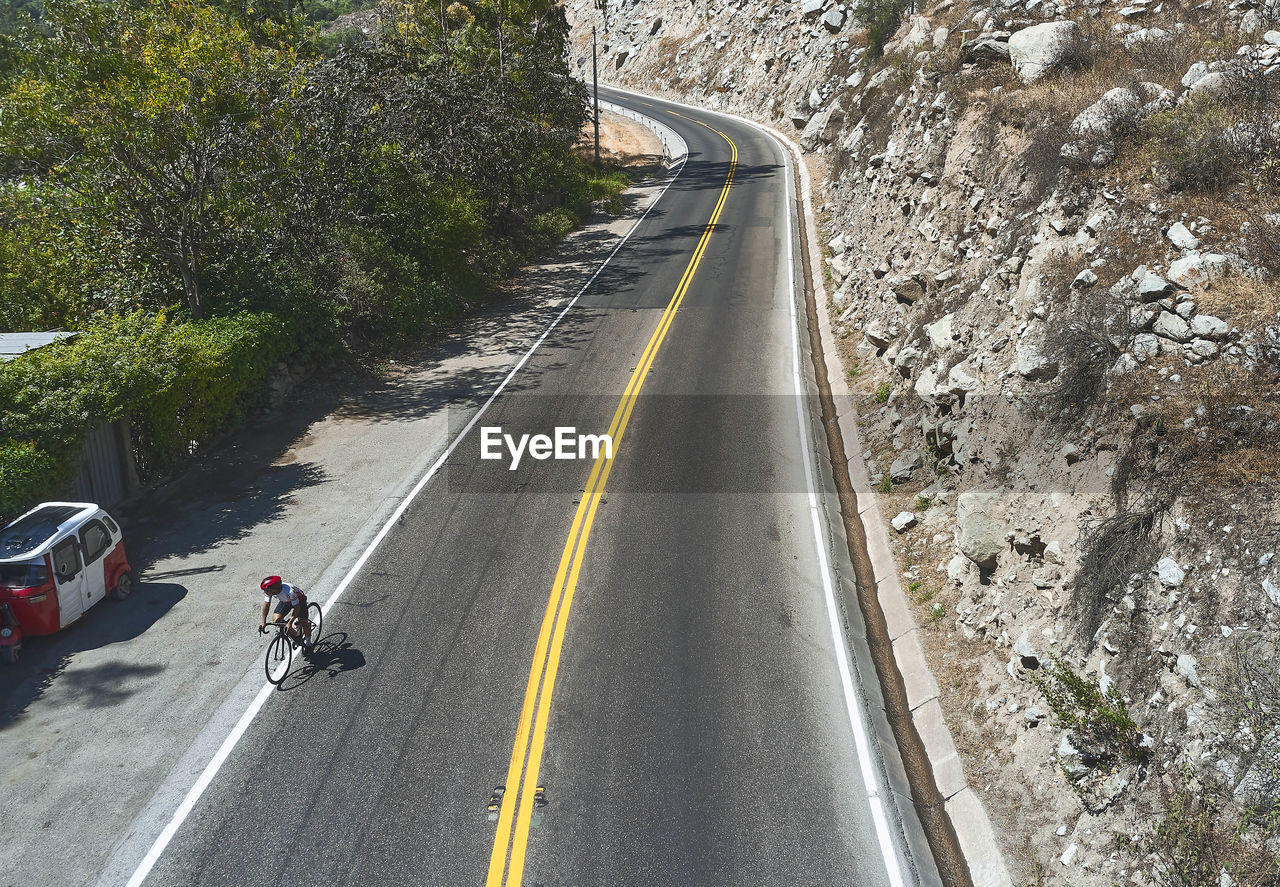 VIEW OF PEOPLE RIDING MOTORCYCLE ON ROAD