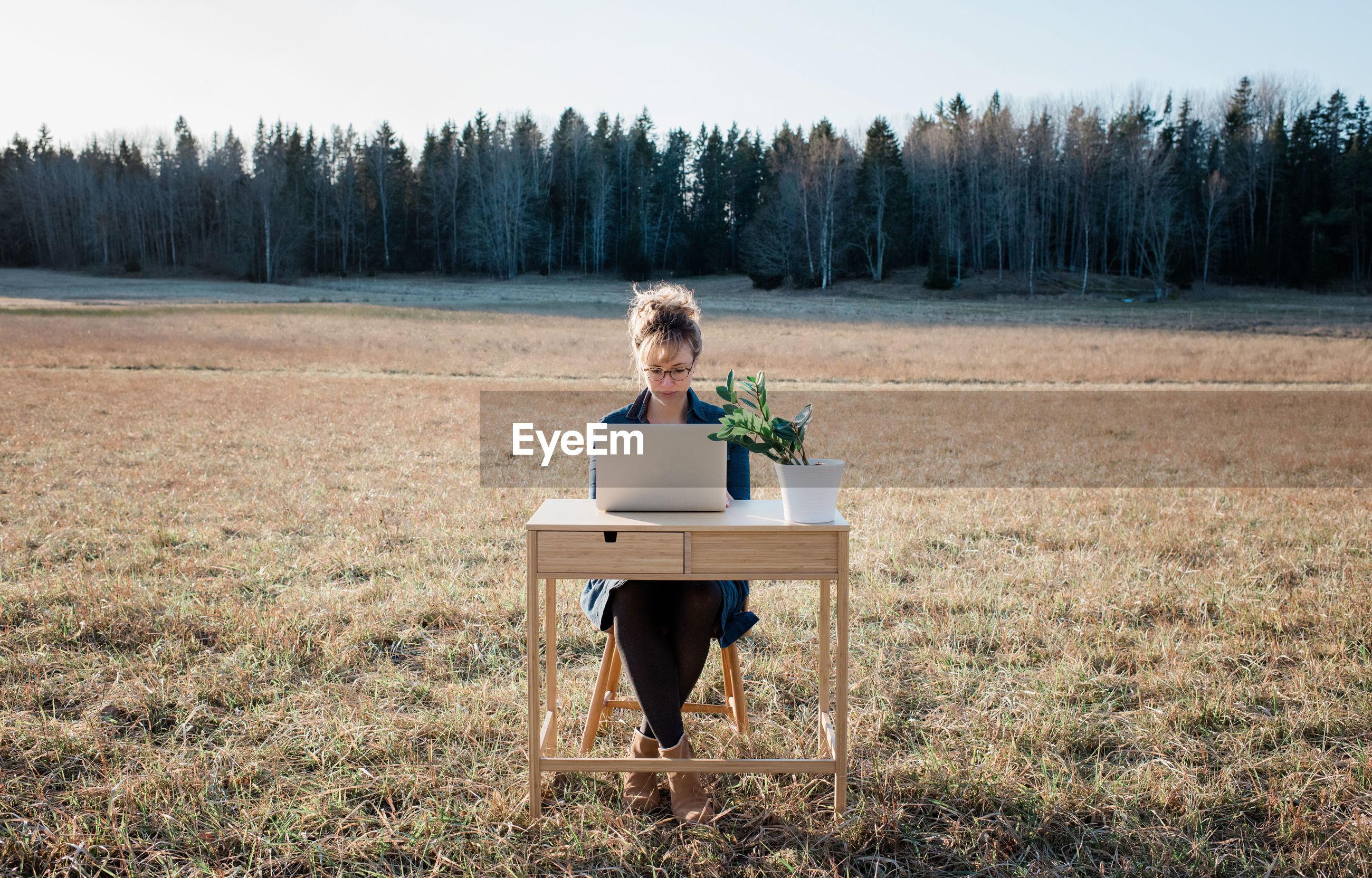 WOMAN SITTING ON SEAT IN FIELD