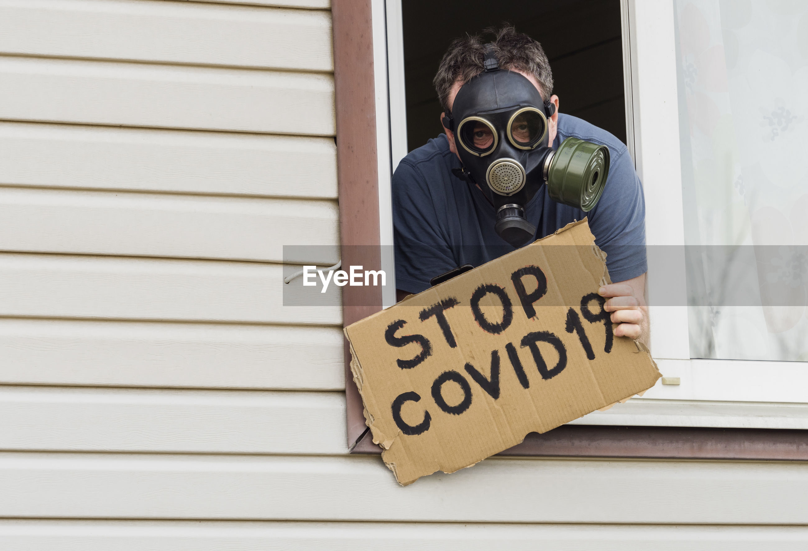 A man in a gas mask shows a poster. stop covid-19