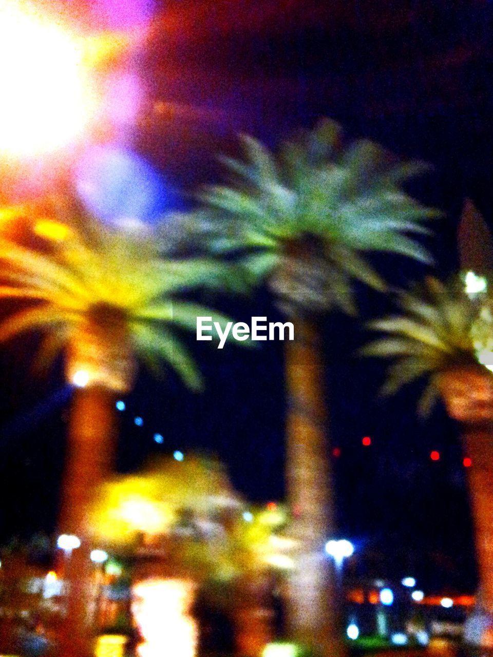 DEFOCUSED VIEW OF ILLUMINATED CITY AT NIGHT
