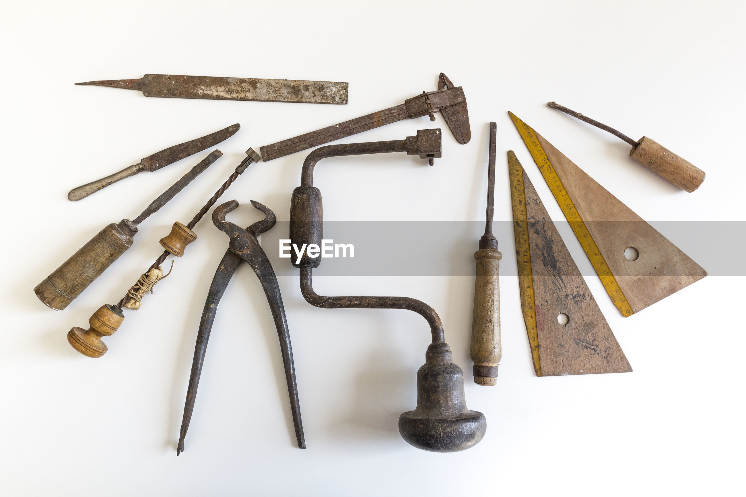 Directly above shot of tools on table against white background