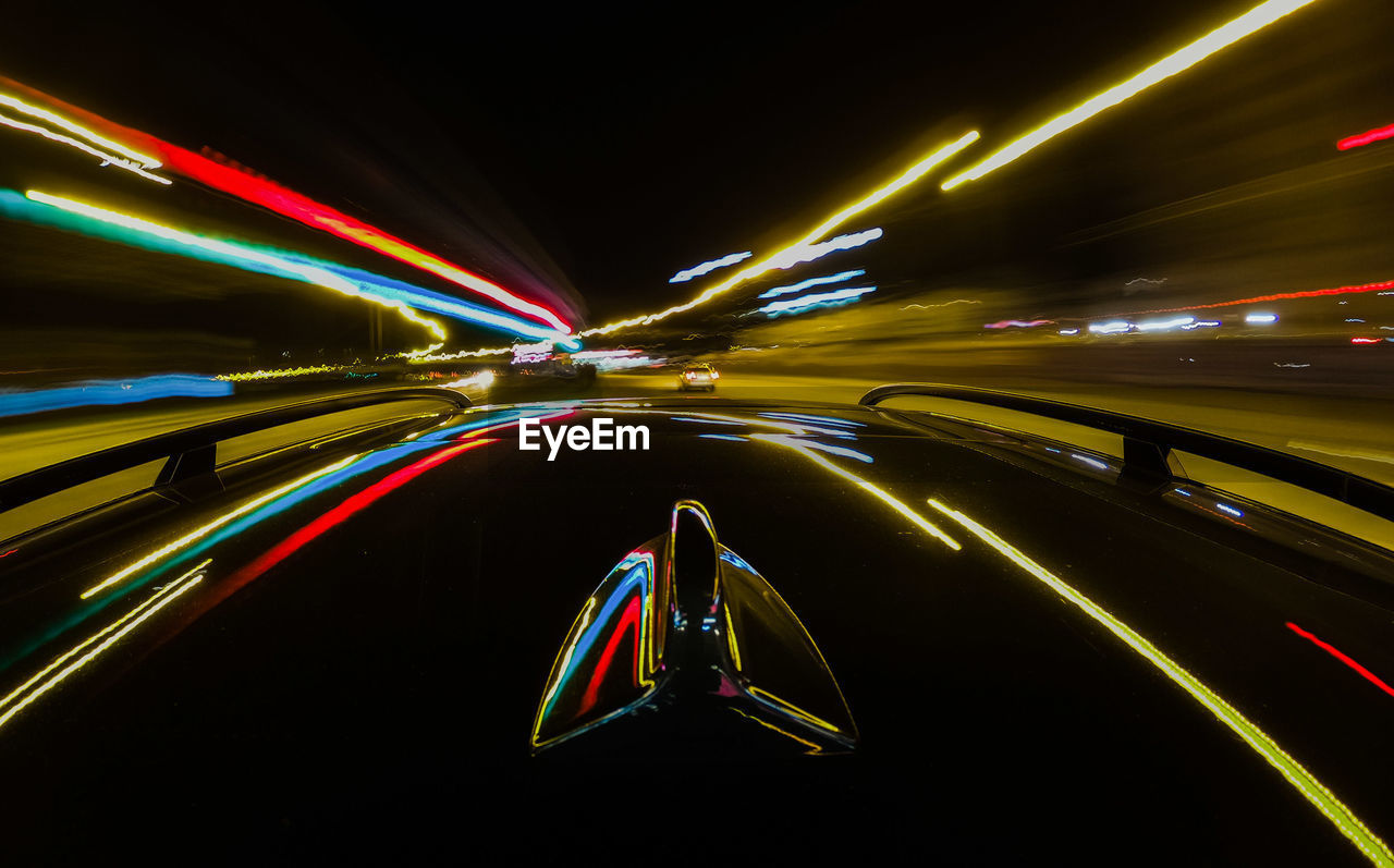 Cropped Image Of Car With Light Trails On Road At Night