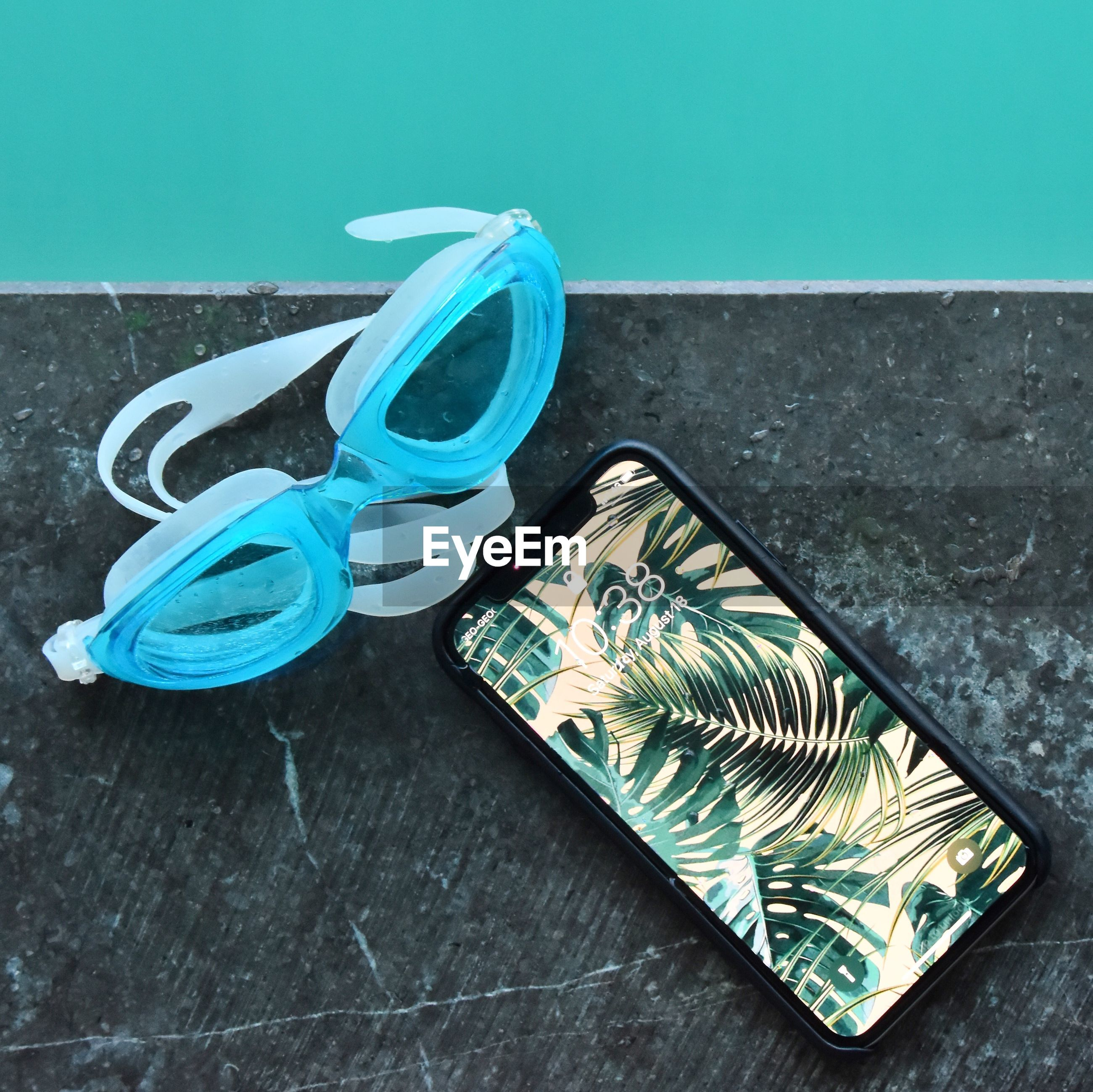 High angle view of swimming goggles and smart phone at poolside