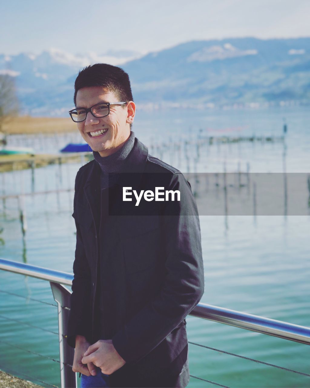 Portrait Of Smiling Man Standing By Lake Against Sky