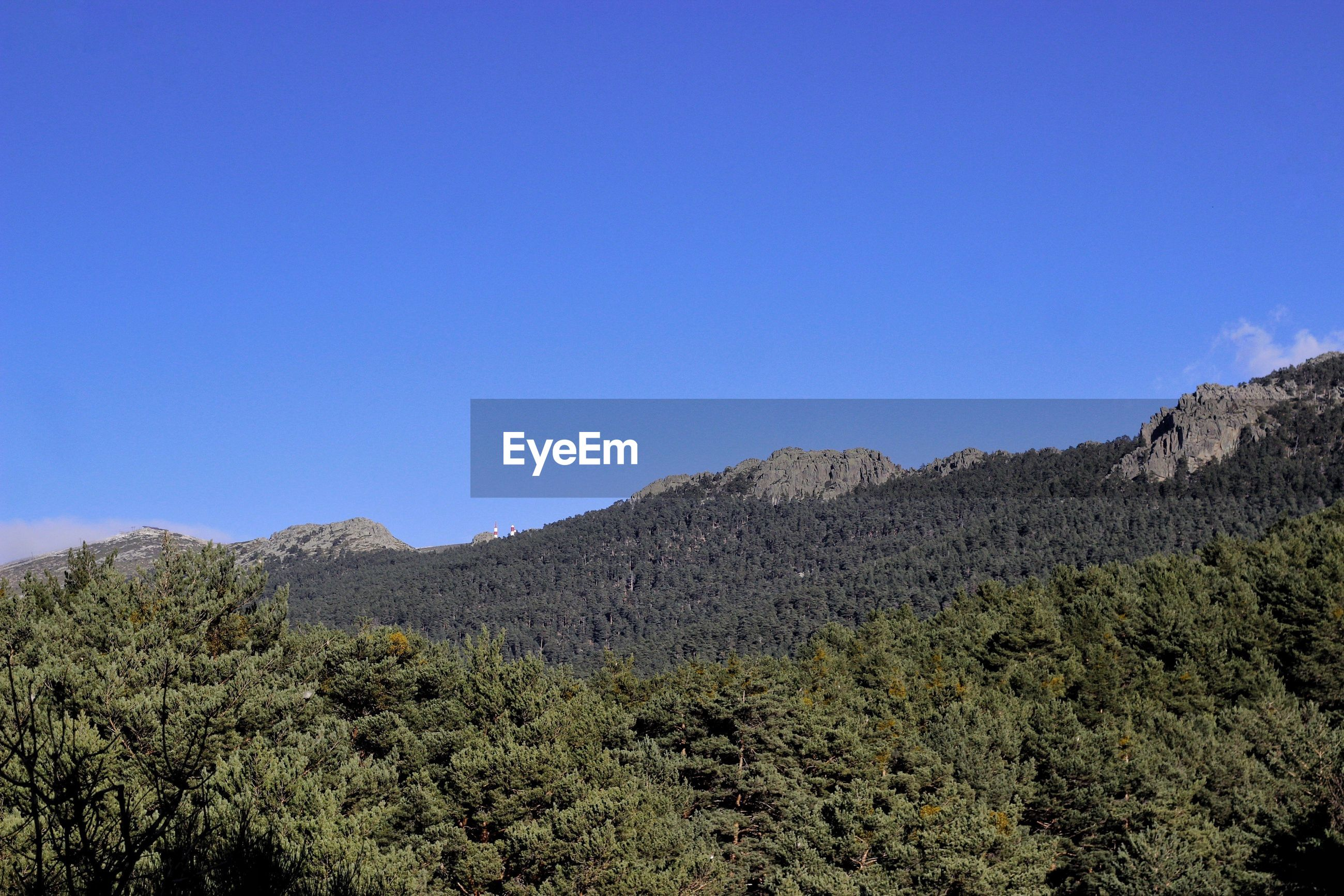 Low angle view of mountains against clear blue sky on sunny day