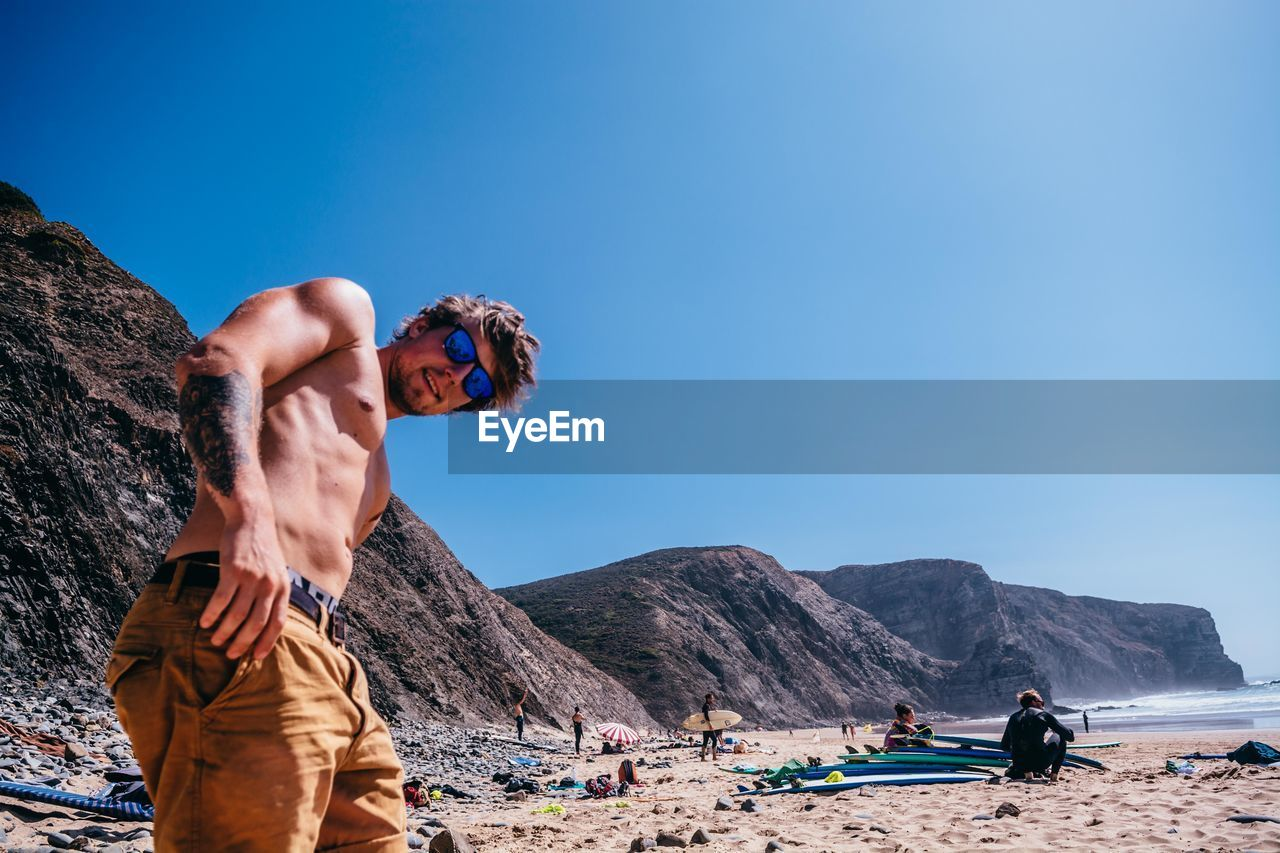 Portrait Of Shirtless Young Man Standing At Beach