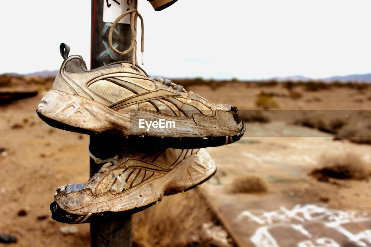 Old Shoes Hanging On Pole At Desert