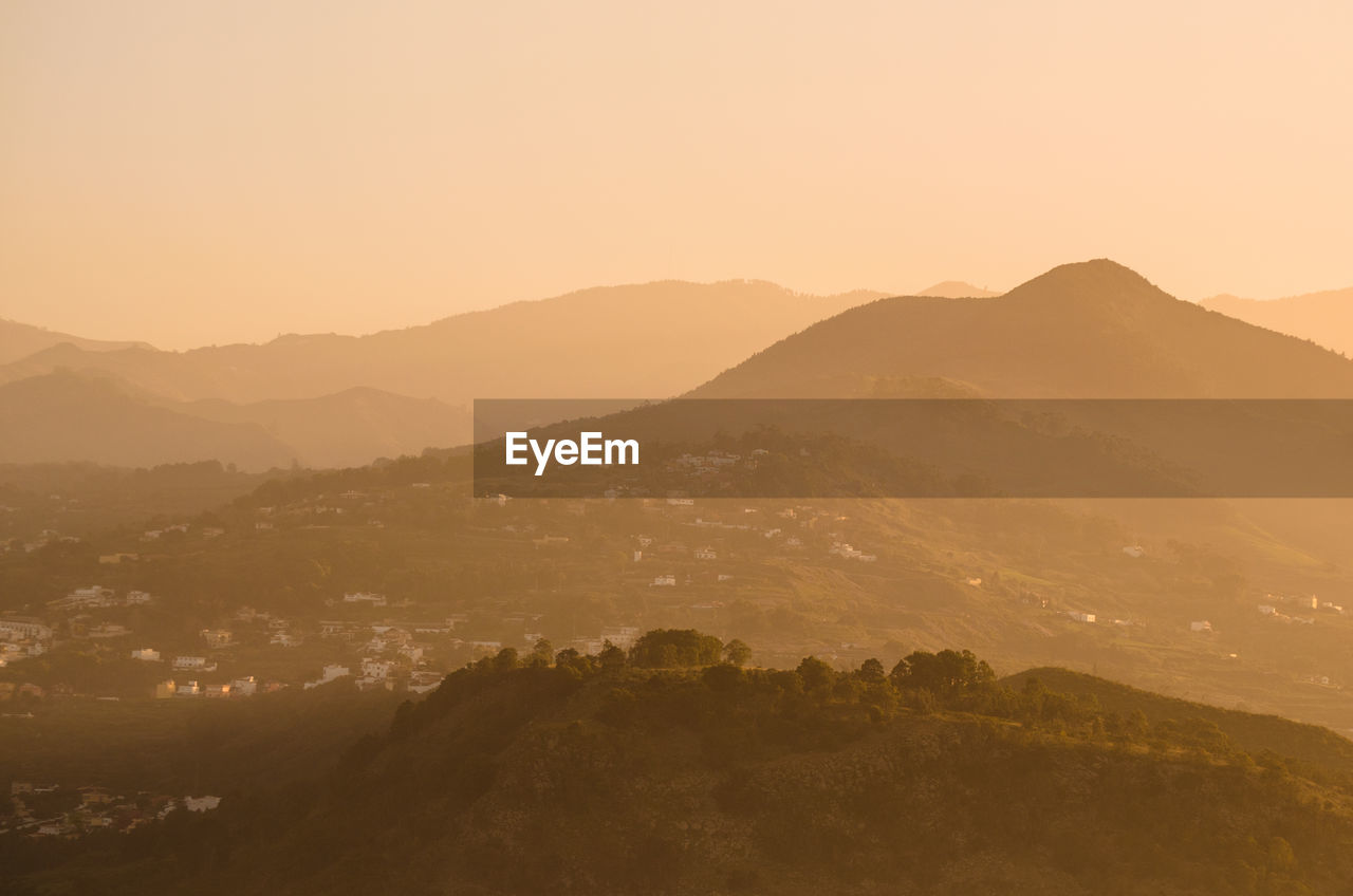 mountain, scenics - nature, beauty in nature, tranquil scene, sky, tranquility, mountain range, environment, landscape, sunset, no people, non-urban scene, nature, idyllic, copy space, clear sky, orange color, tree, plant, outdoors, hazy
