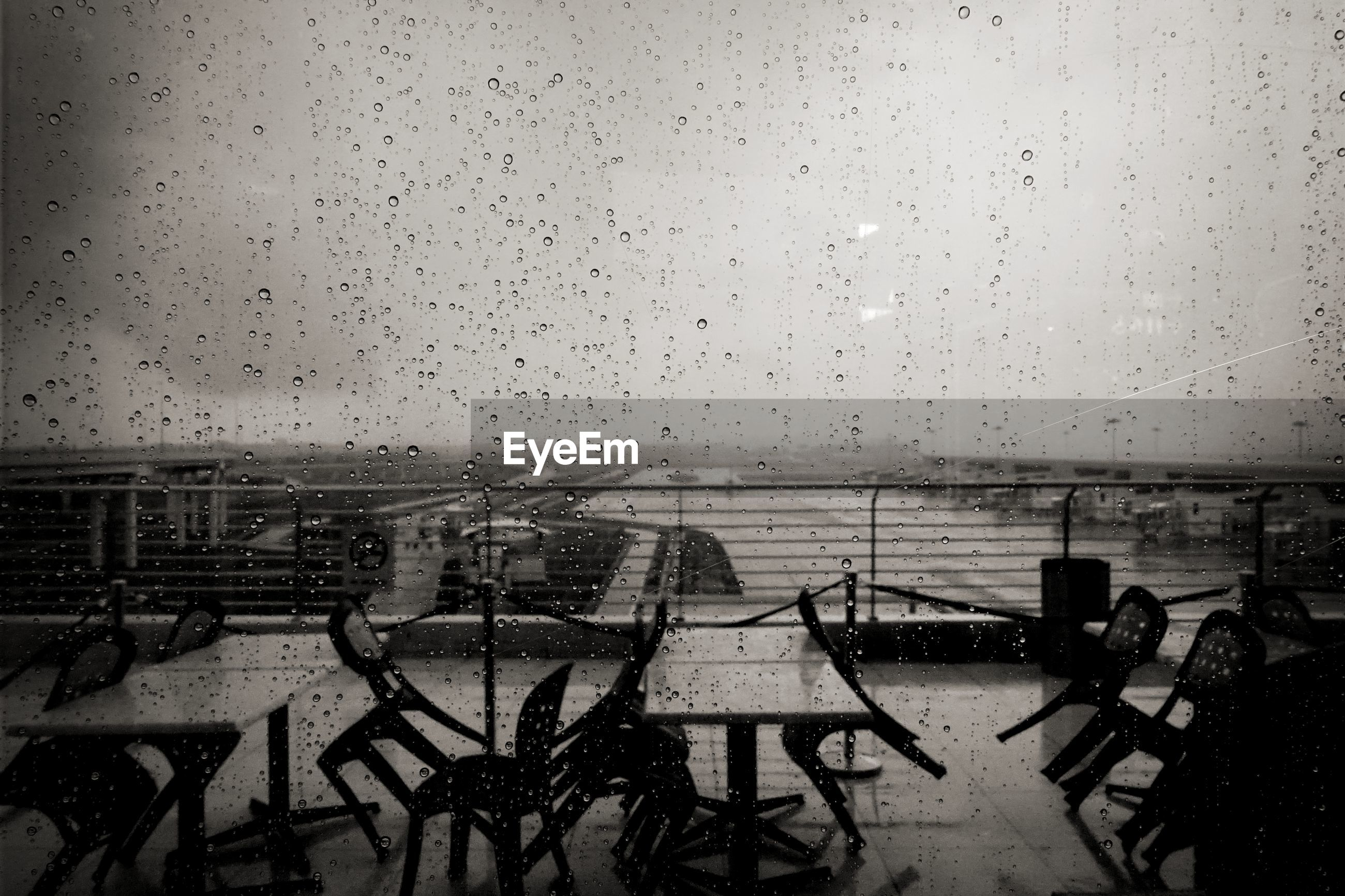 Empty tables and chairs seen through wet glass window against sky during monsoon
