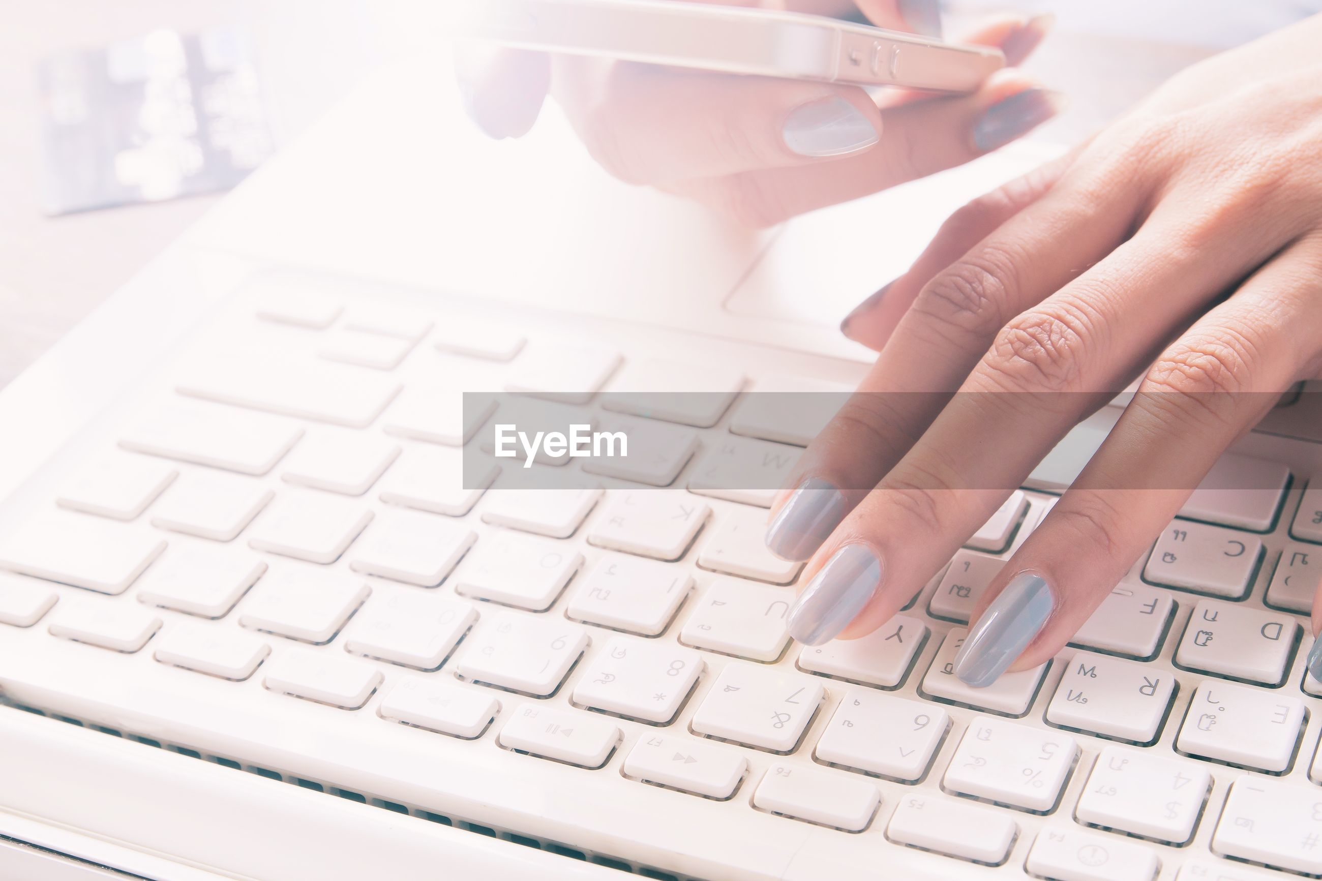 Cropped hands of woman using laptop