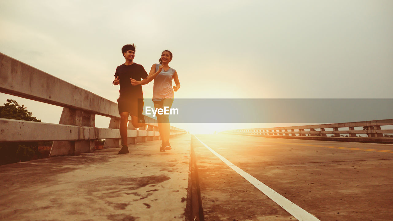 sky, real people, lifestyles, sunset, nature, two people, young adult, leisure activity, women, adult, connection, standing, sunlight, young men, people, transportation, men, architecture, young women, full length, outdoors, bridge - man made structure, lens flare, couple - relationship