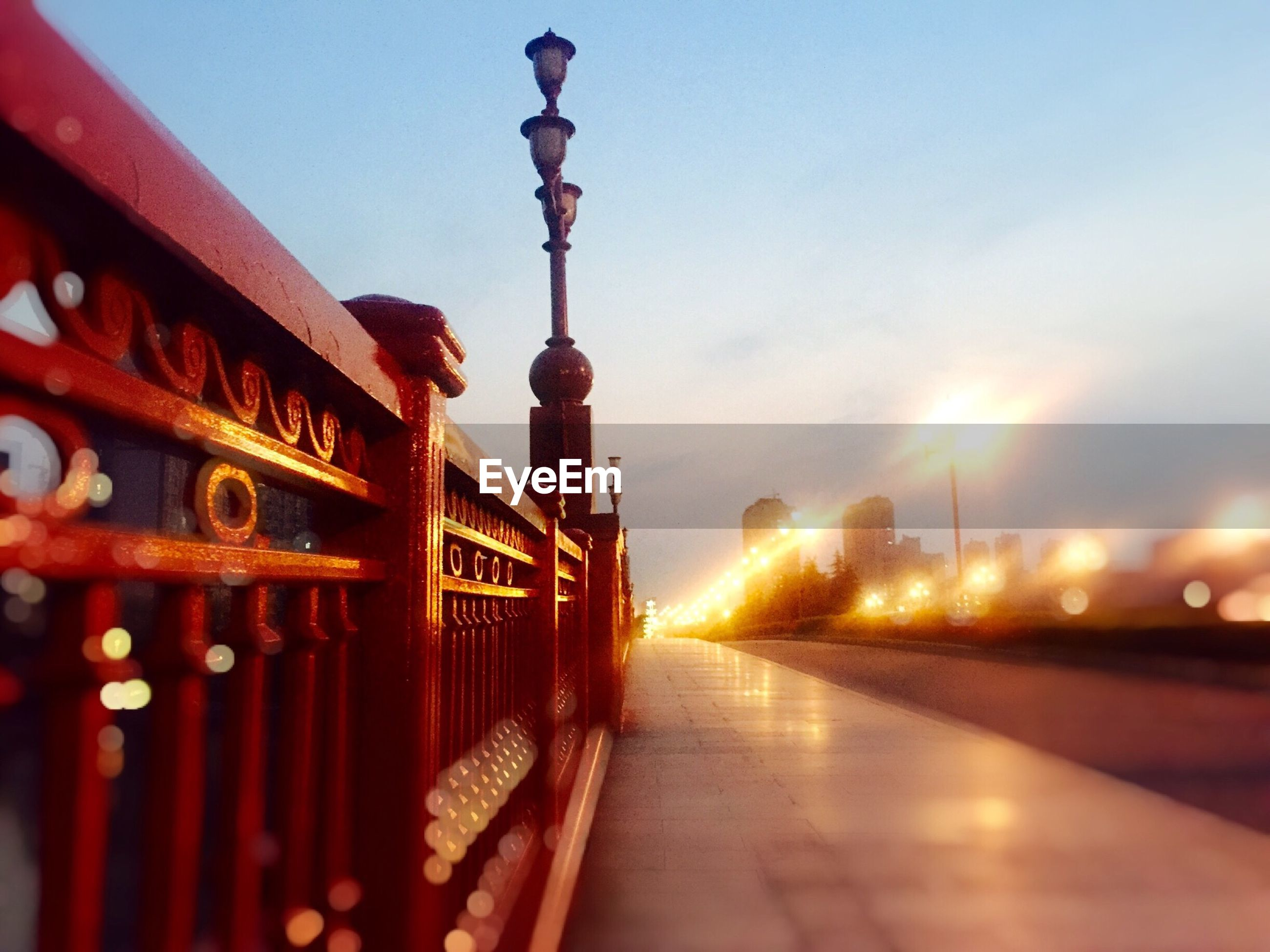 architecture, built structure, illuminated, lighting equipment, street light, sky, building exterior, the way forward, transportation, railing, dusk, travel destinations, travel, city, diminishing perspective, connection, outdoors, sunset, incidental people, vanishing point