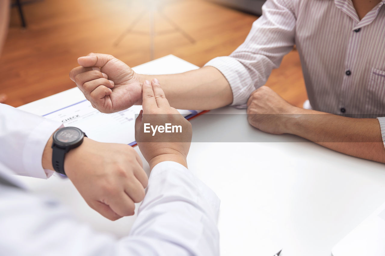 occupation, human hand, real people, men, indoors, human body part, hand, doctor, healthcare and medicine, two people, people, expertise, adult, midsection, table, medical supplies, lab coat, professional occupation, cooperation, holding