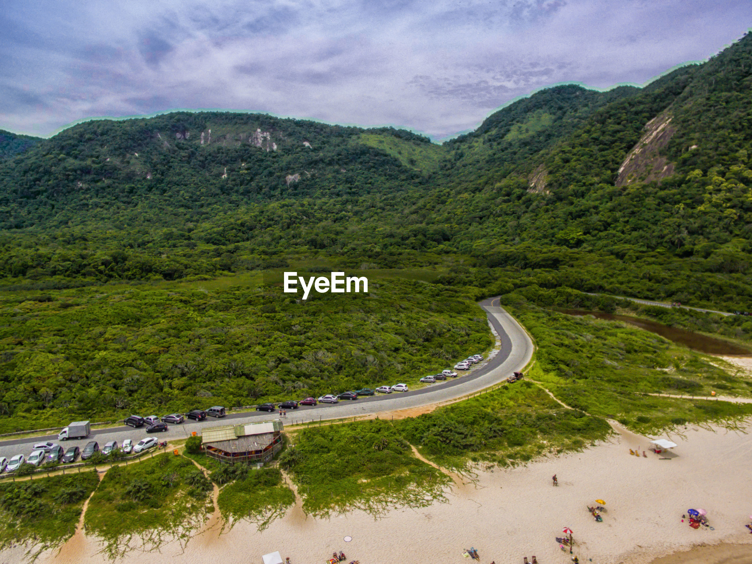 HIGH ANGLE VIEW OF WINDING ROAD BY MOUNTAIN AGAINST SKY