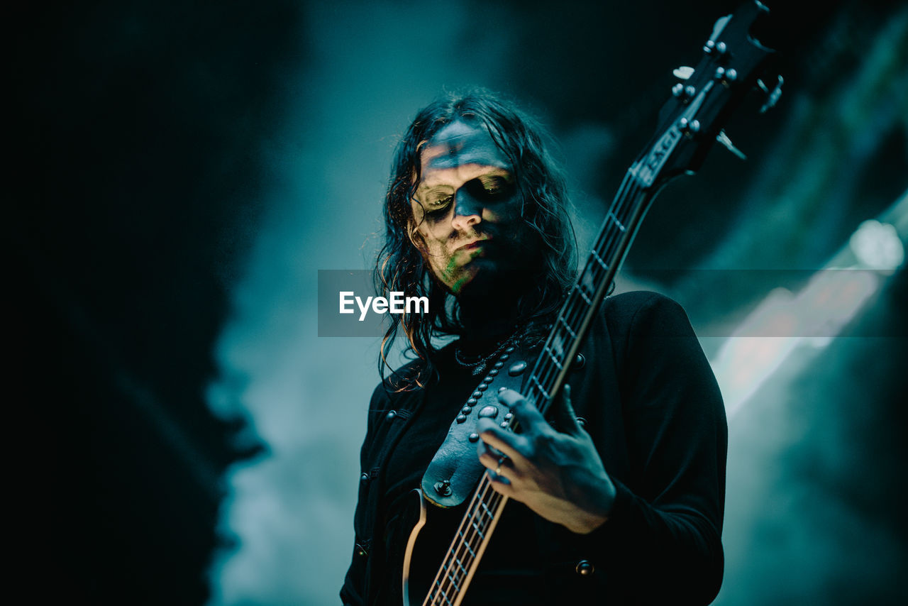 music, musician, arts culture and entertainment, performance, string instrument, musical instrument, one person, guitar, artist, playing, guitarist, long hair, waist up, musical equipment, singing, low angle view, rock music, rock musician, stage - performance space, stage, popular music concert, plucking an instrument, electric guitar, hairstyle, nightlife
