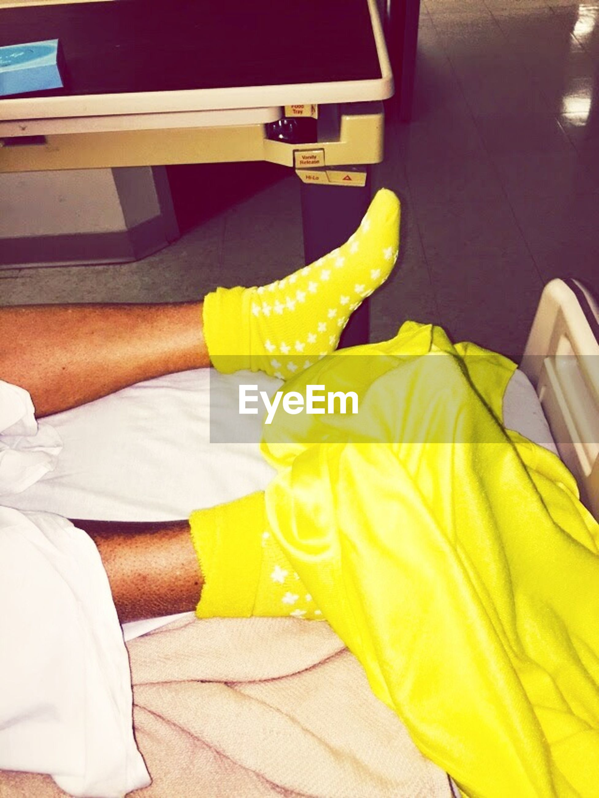 yellow, low section, indoors, person, relaxation, lifestyles, casual clothing, leisure activity, high angle view, men, personal perspective, sitting, part of, cropped, holding, day
