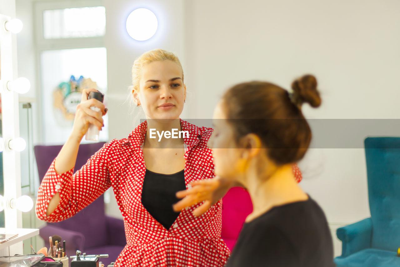 Beautician applying hairspray to customer