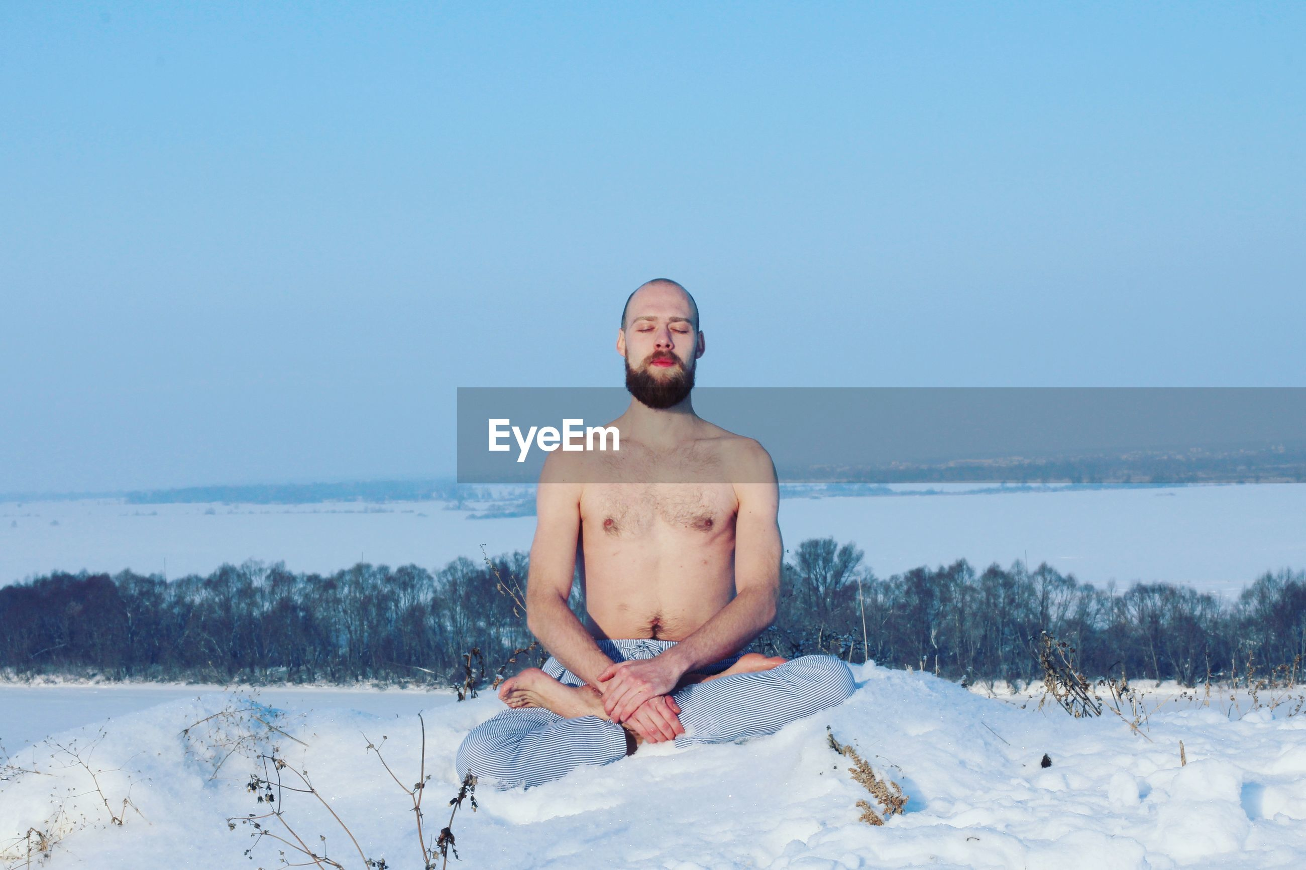 Shirtless young man meditating on snow against clear sky
