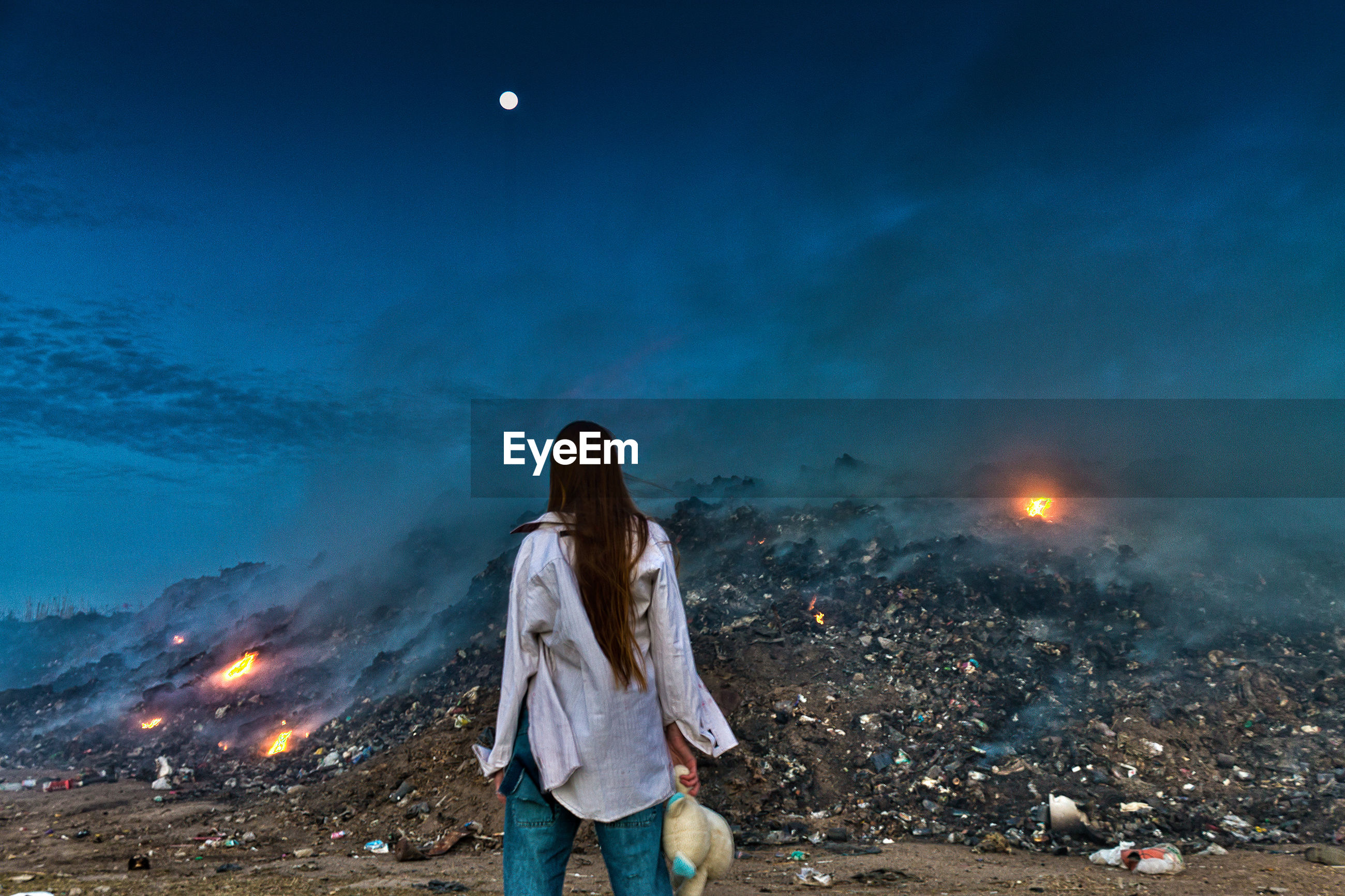 Rear view of woman standing against junkyard at night