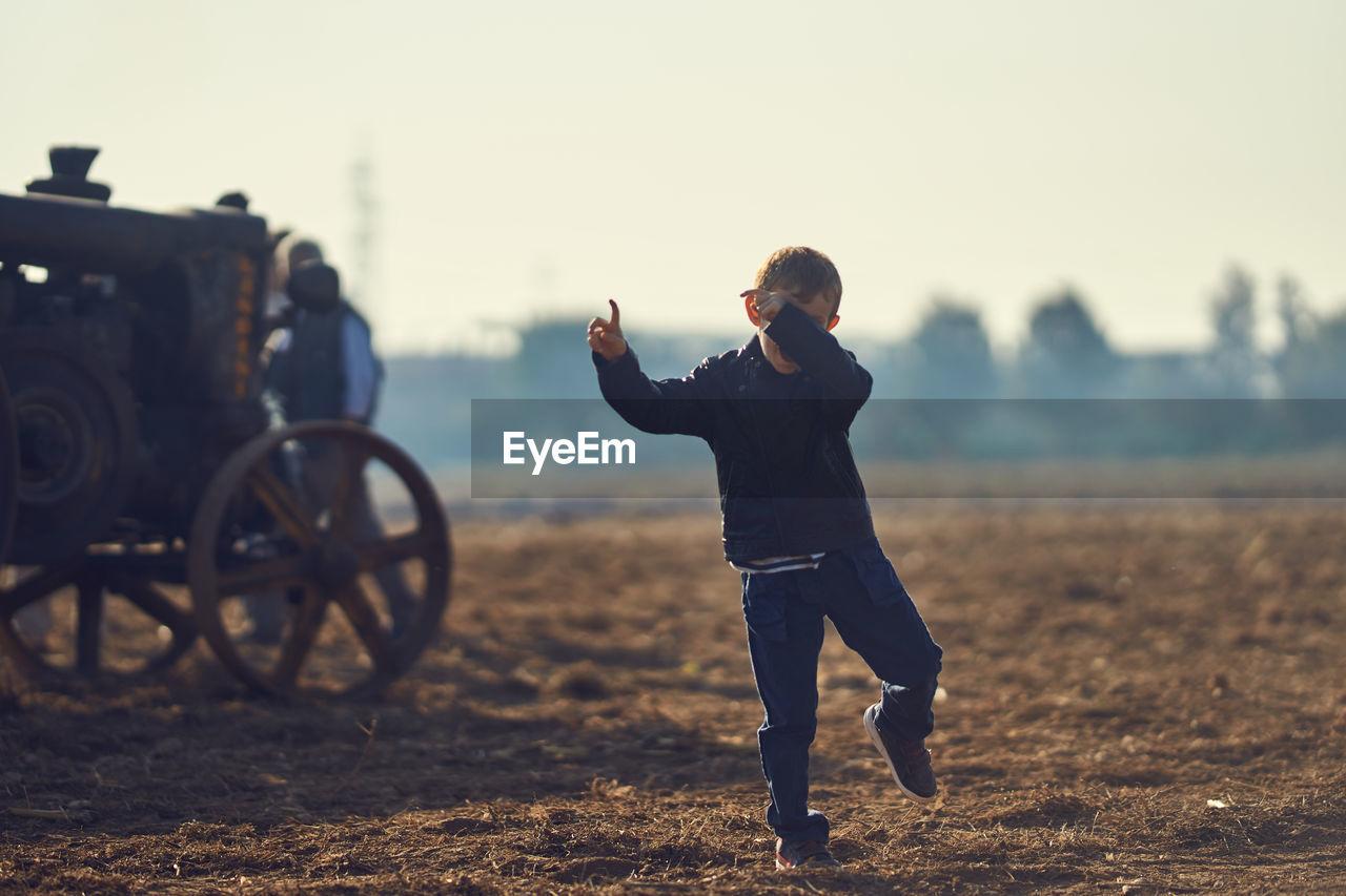 Boy Dancing On Dirt Field