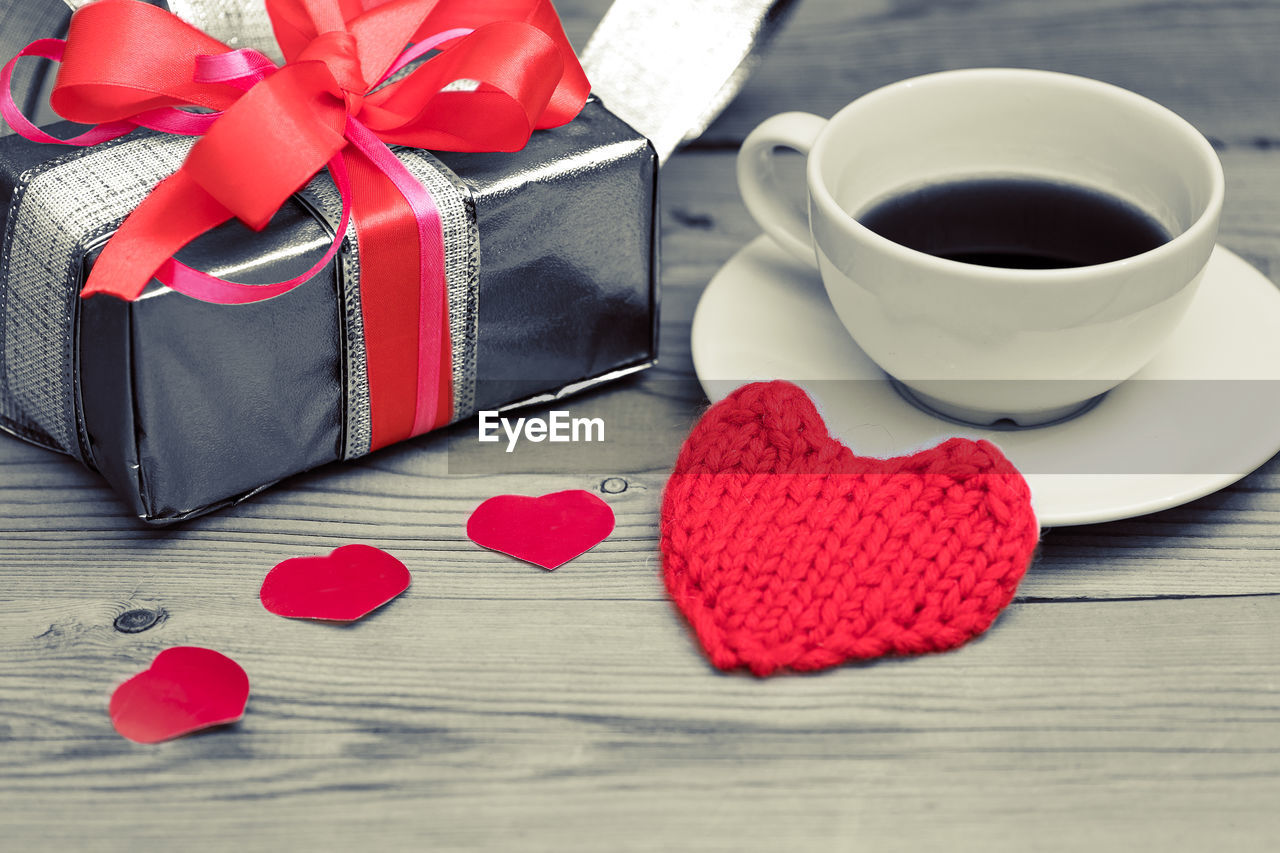 cup, red, coffee cup, mug, coffee - drink, drink, table, still life, heart shape, coffee, food and drink, ribbon, refreshment, ribbon - sewing item, paper, indoors, love, high angle view, close-up, no people, positive emotion, box - container, crockery, valentine's day - holiday