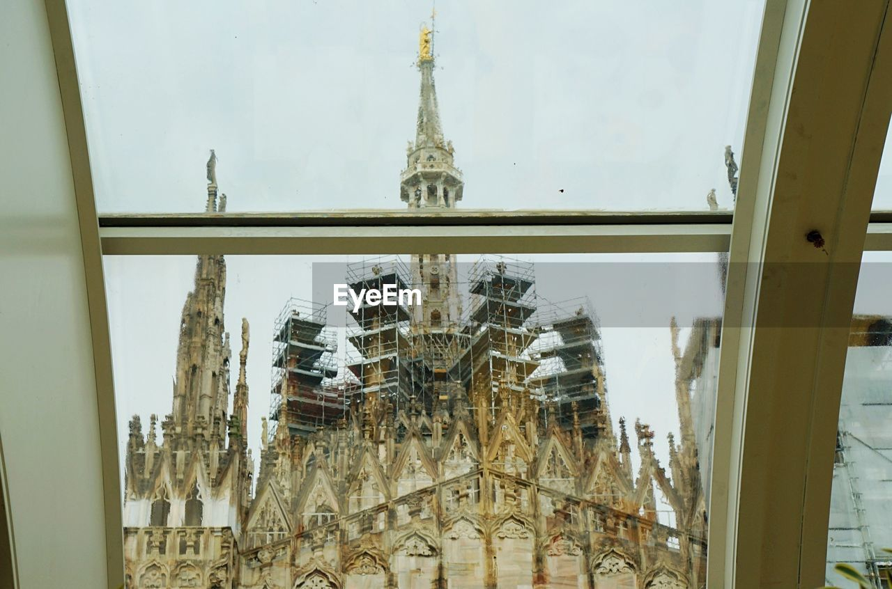 Low angle view of milan cathedral against sky seen from skylight