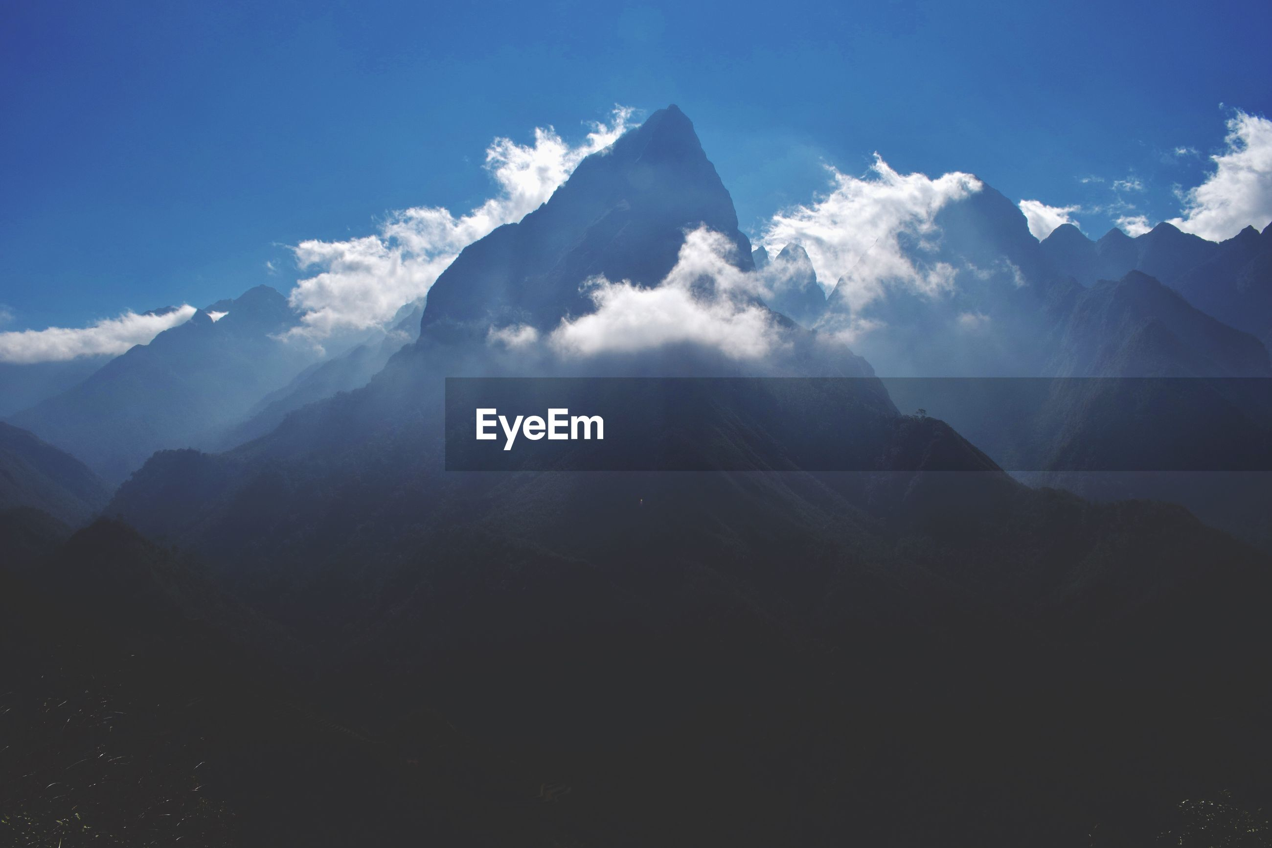 SCENIC VIEW OF CLOUDS OVER MOUNTAIN AGAINST SKY