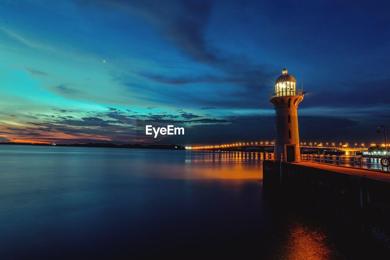 Illuminated Lighthouse By Sea Against Cloudy Sky At Dusk