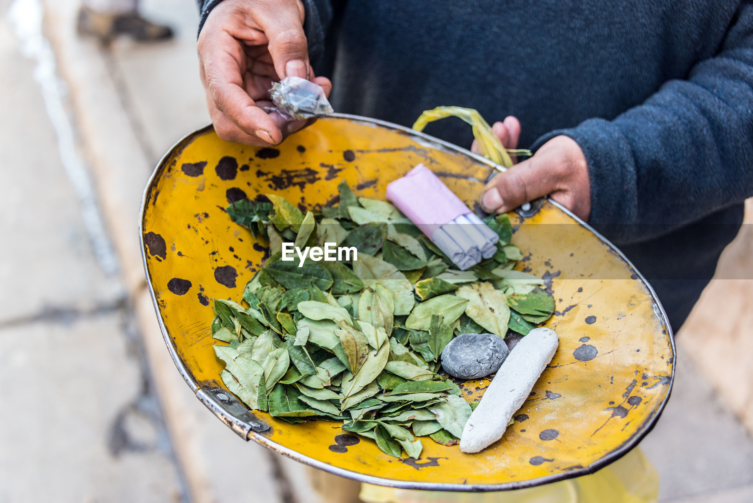 Midsection of person holding coca leaves and cigarettes in plate