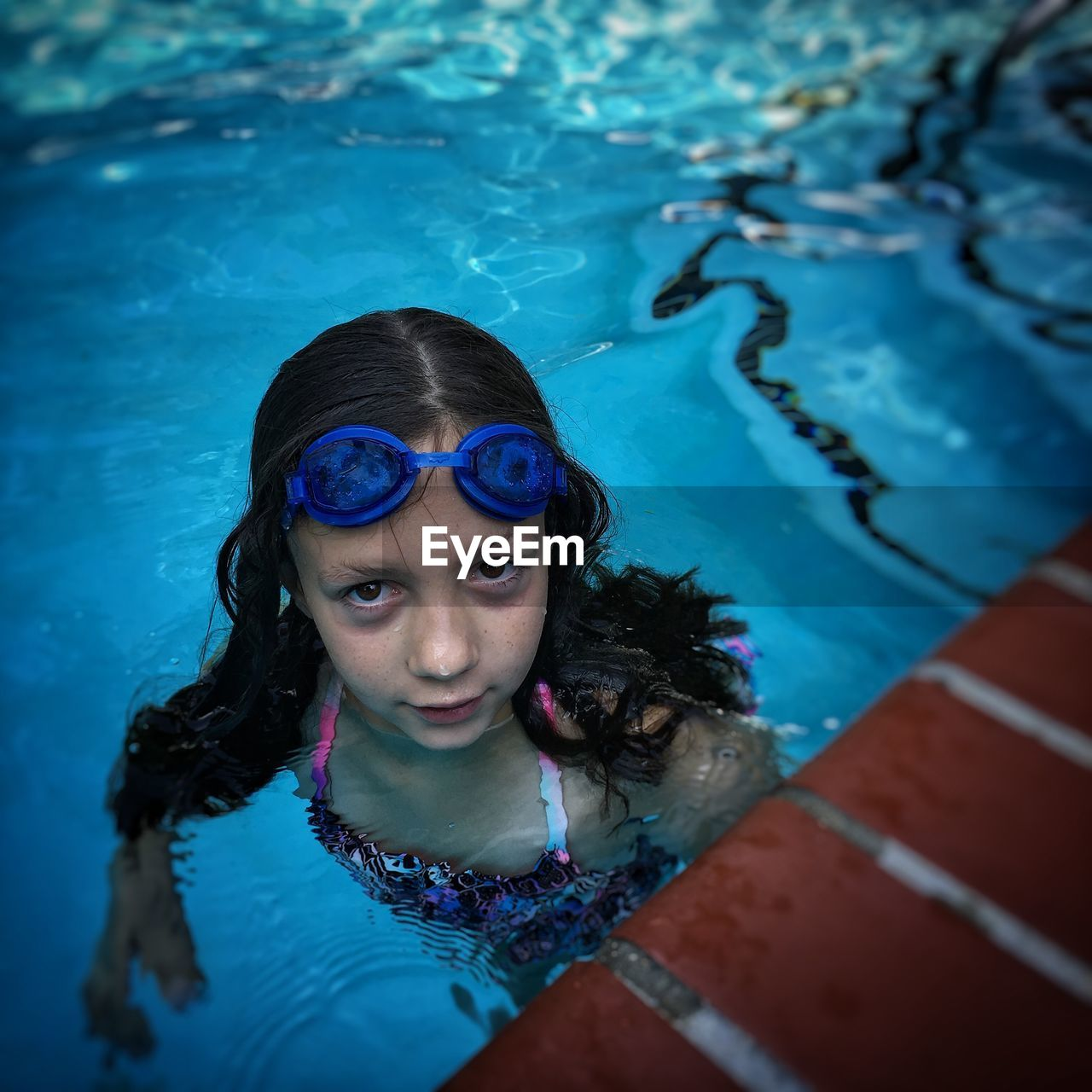 child, water, childhood, one person, real people, girls, portrait, swimming pool, females, pool, looking at camera, lifestyles, leisure activity, swimming, swimwear, women, front view, innocence, outdoors, hairstyle, eyewear