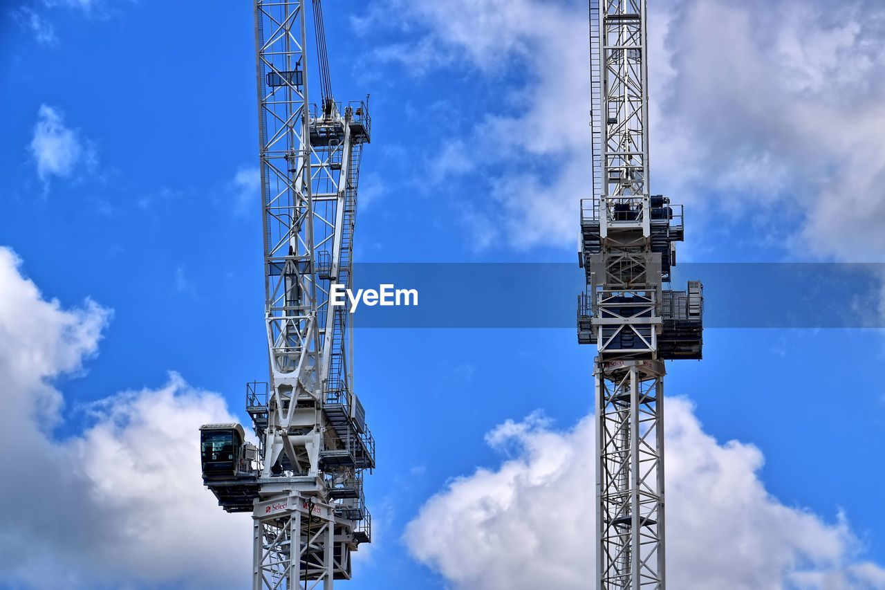 LOW ANGLE VIEW OF CRANES AGAINST SKY
