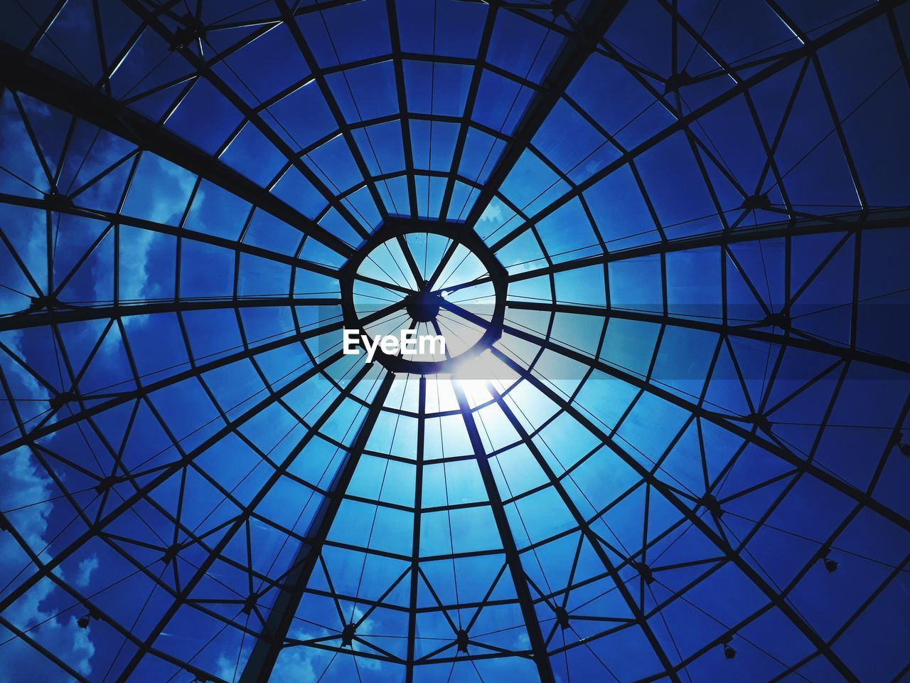 geometric shape, pattern, built structure, low angle view, architecture, shape, blue, circle, indoors, glass - material, sky, sunlight, ceiling, design, no people, full frame, directly below, day, skylight, backgrounds, modern, architecture and art, cupola, ornate