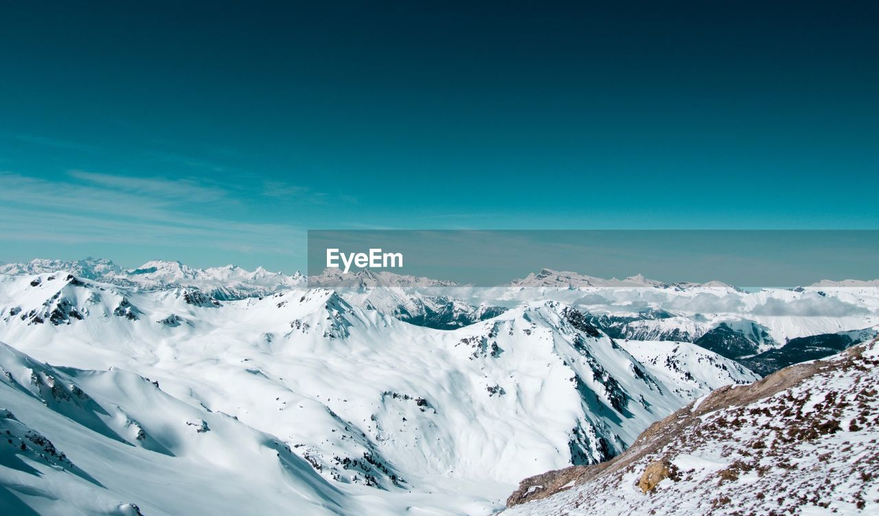 beauty in nature, snow, nature, cold temperature, tranquil scene, winter, scenics, tranquility, mountain, blue, outdoors, day, sky, no people, landscape, sunlight, mountain range, snowcapped mountain, cloud - sky