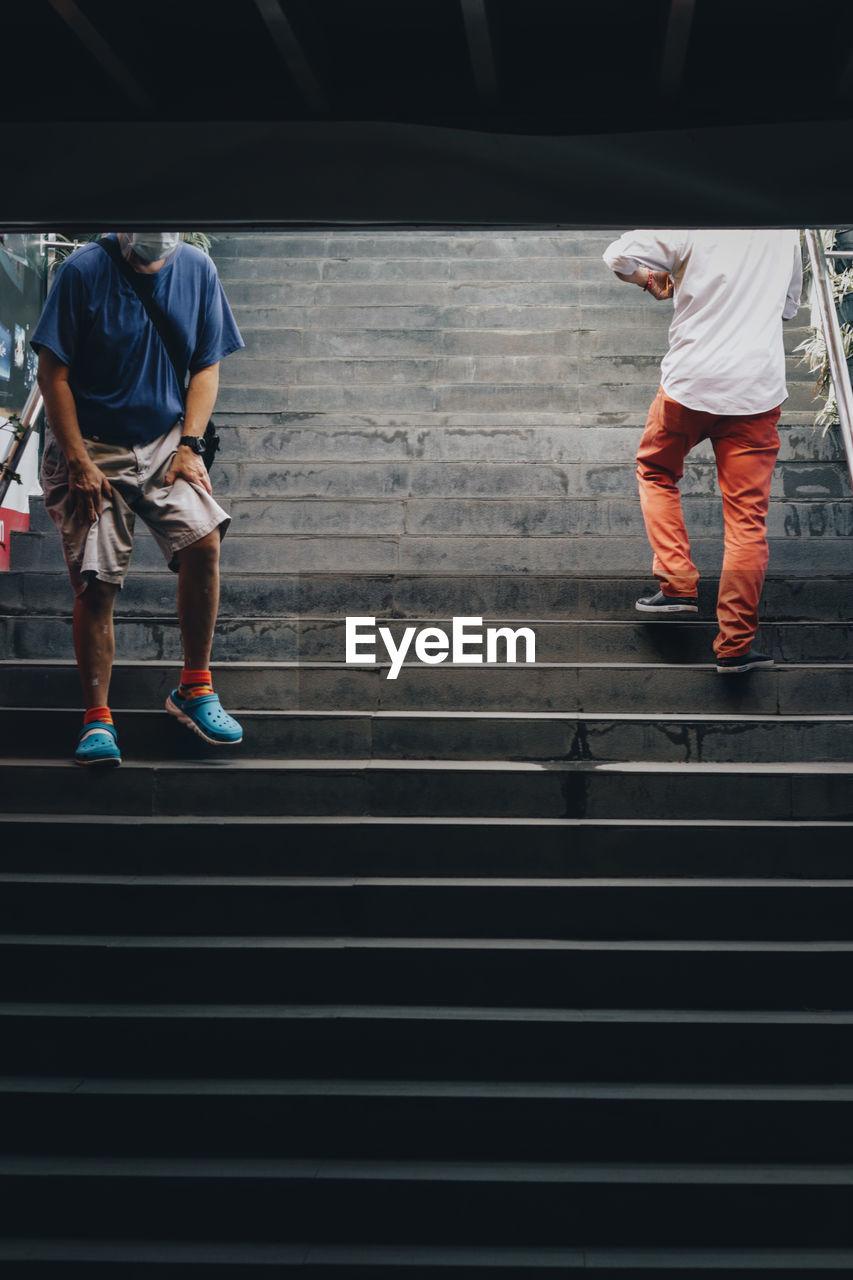 REAR VIEW OF MEN WALKING ON STEPS