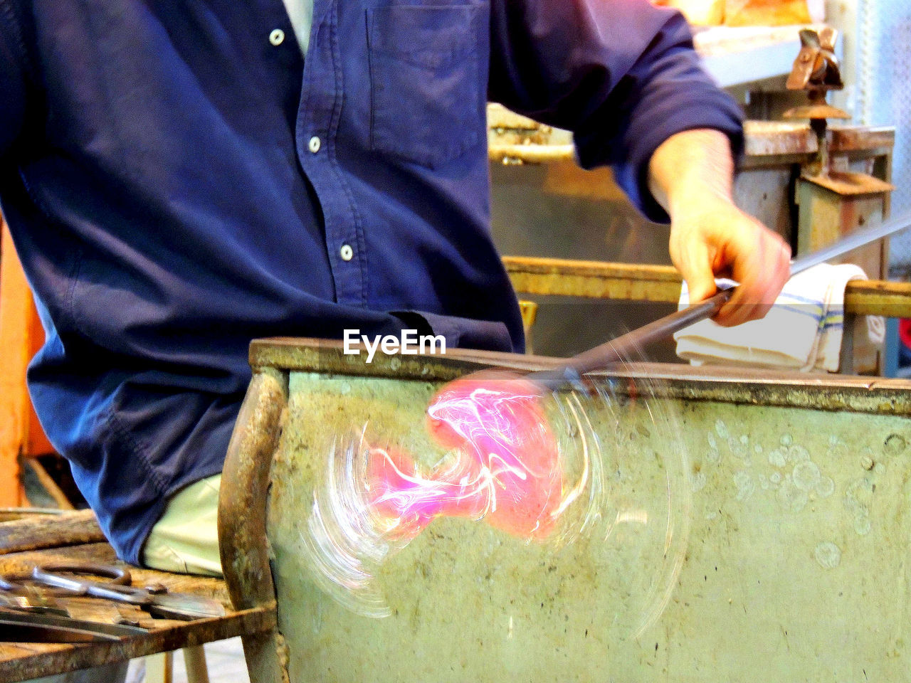 Midsection Of Worker Spinning Glass Blower At Factory