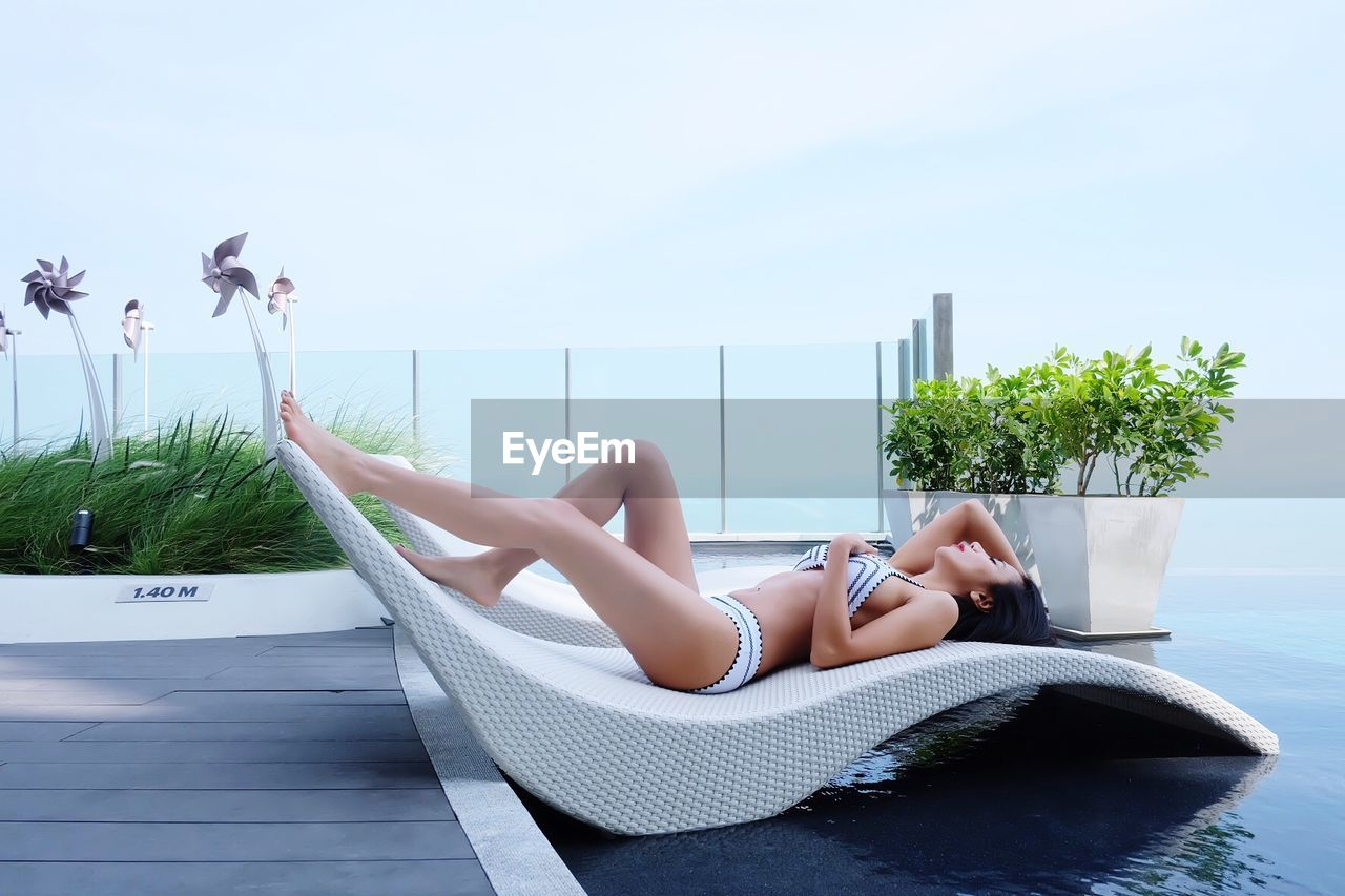 Woman lying on lounger at poolside against sky